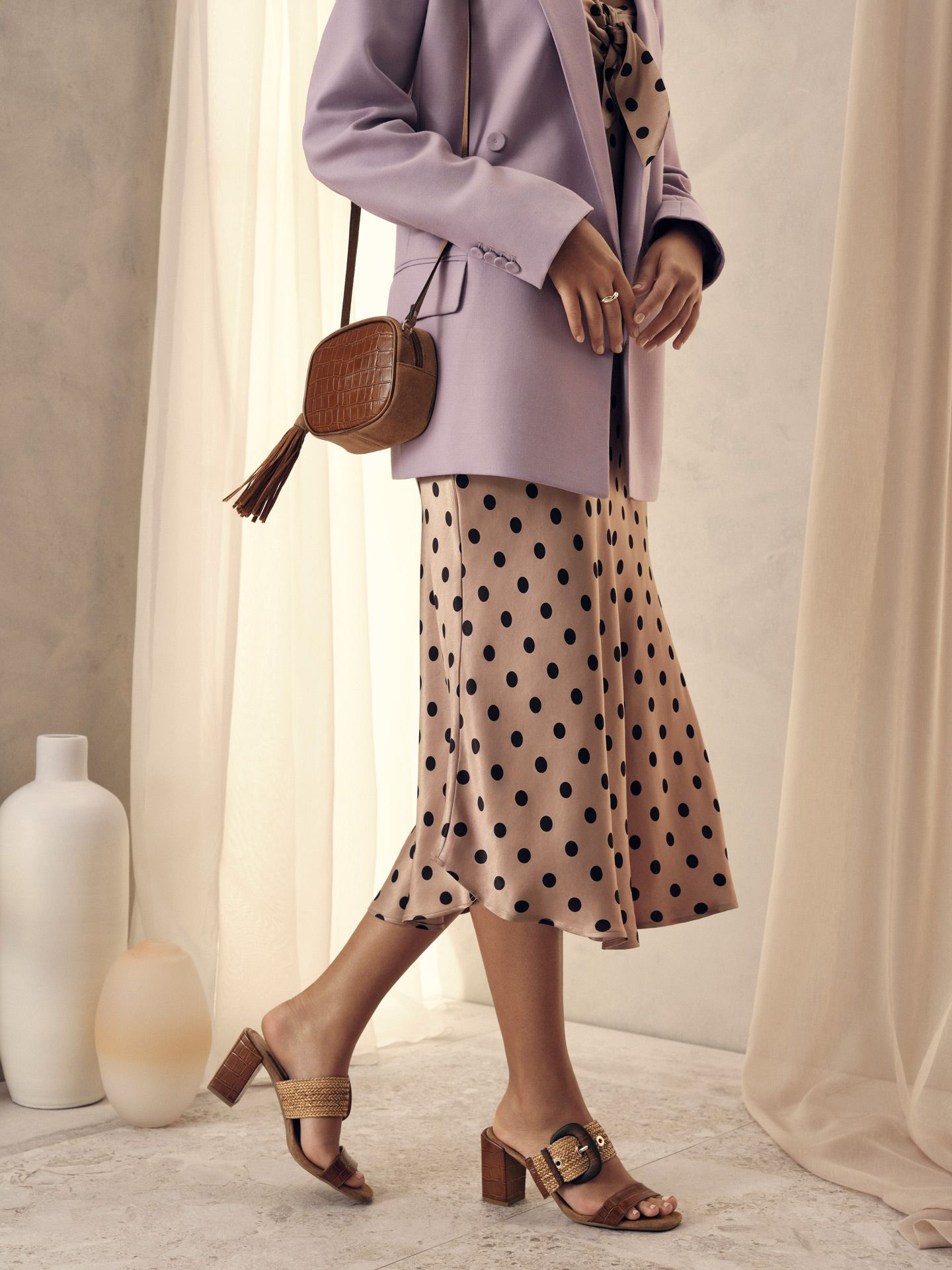 model of colour wearing polka dot skirt and light purple jacket with open-toed summer shoes for Jean-Paul Fortin summer-spring collection photographed by Maxyme G Delisle with artistic direction, conception and set design by Studio TB