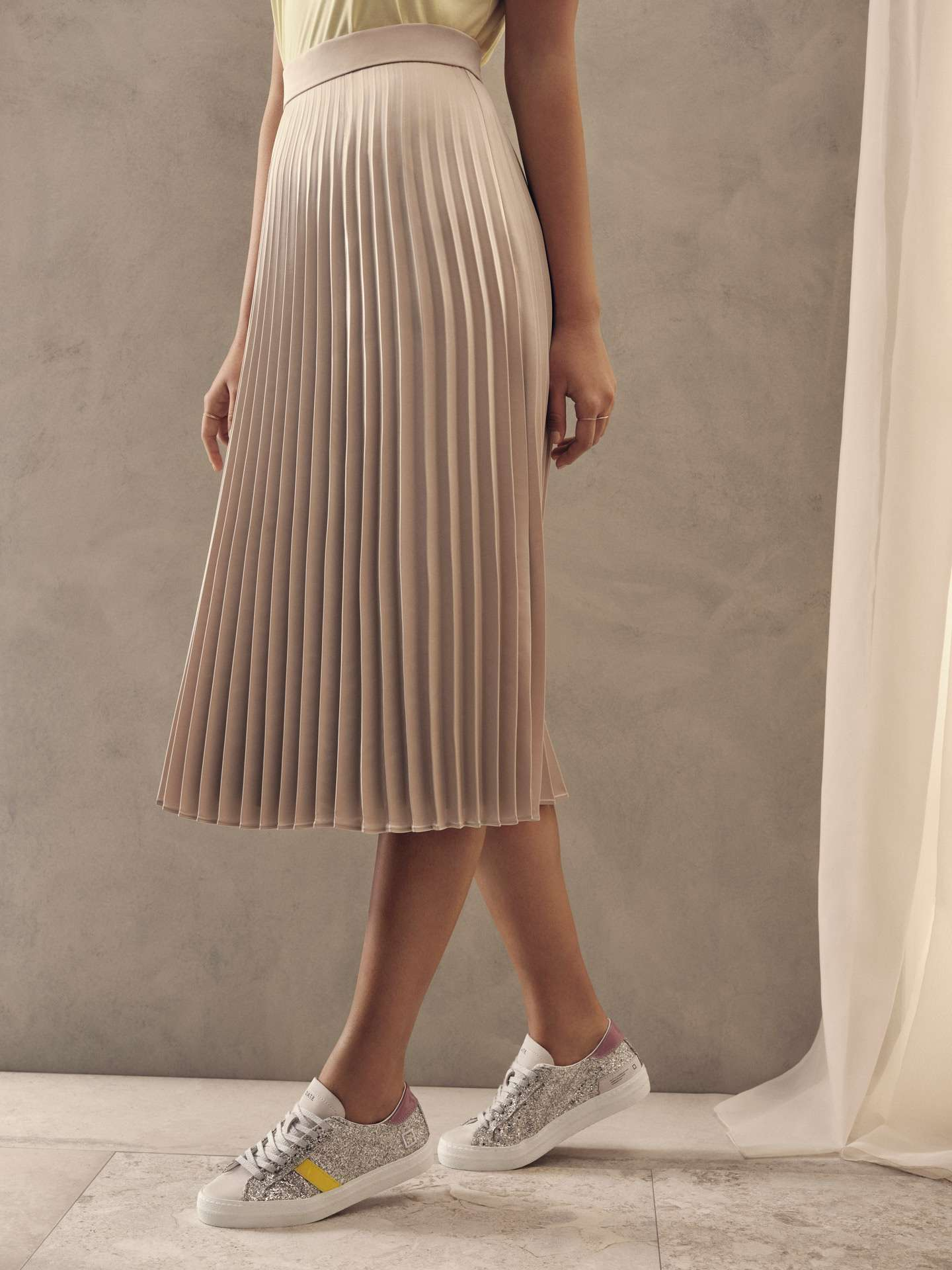 model of colour wearing pleated midi skirt with silver glitter sneakers for Jean-Paul Fortin summer-spring collection photographed by Maxyme G Delisle with artistic direction, conception and set design by Studio TB