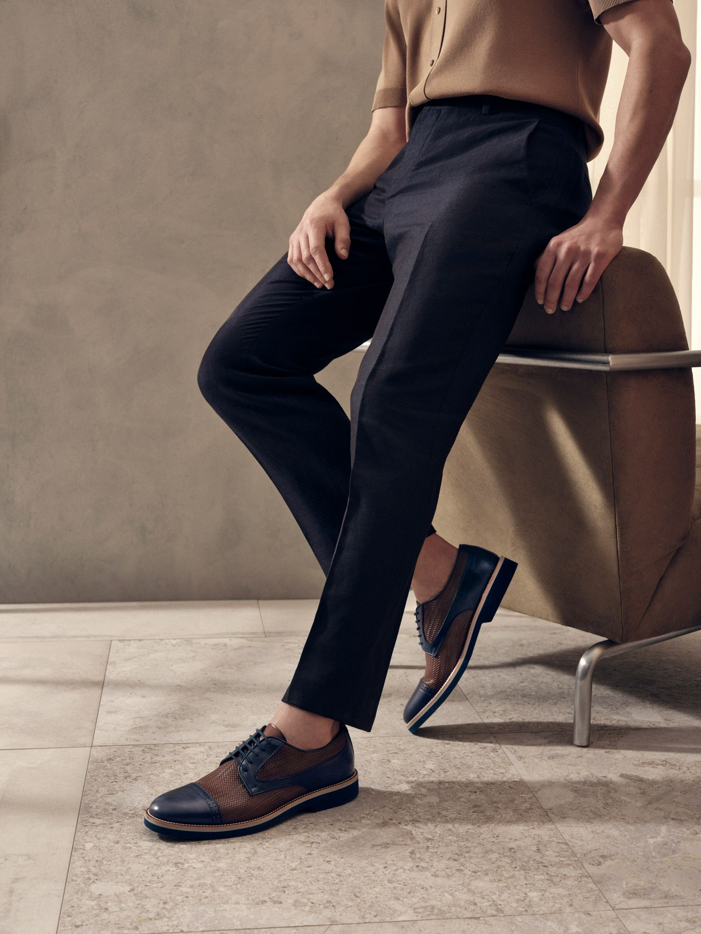 male model wearing dark blue formal pants with brown and dark blue leather formal shoes leaning against chair for Jean-Paul Fortin summer-spring collection photographed by Maxyme G Delisle with artistic direction, conception and set design by Studio TB