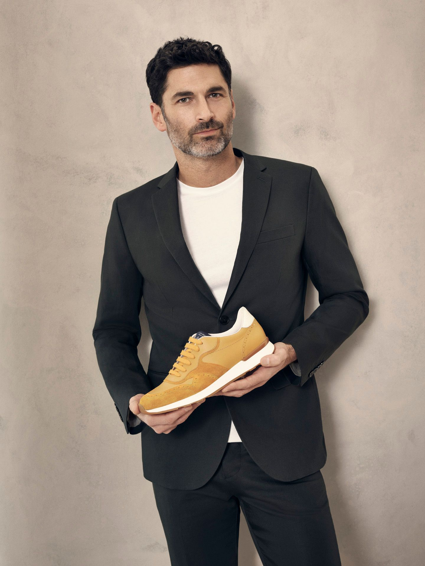 portrait of middle aged man wearing white t-shirt with black suit jacket and formal black pants holding a yellow sneaker for Jean-Paul Fortin summer-spring collection photographed by Maxyme G Delisle with artistic direction, conception and set design by Studio TB
