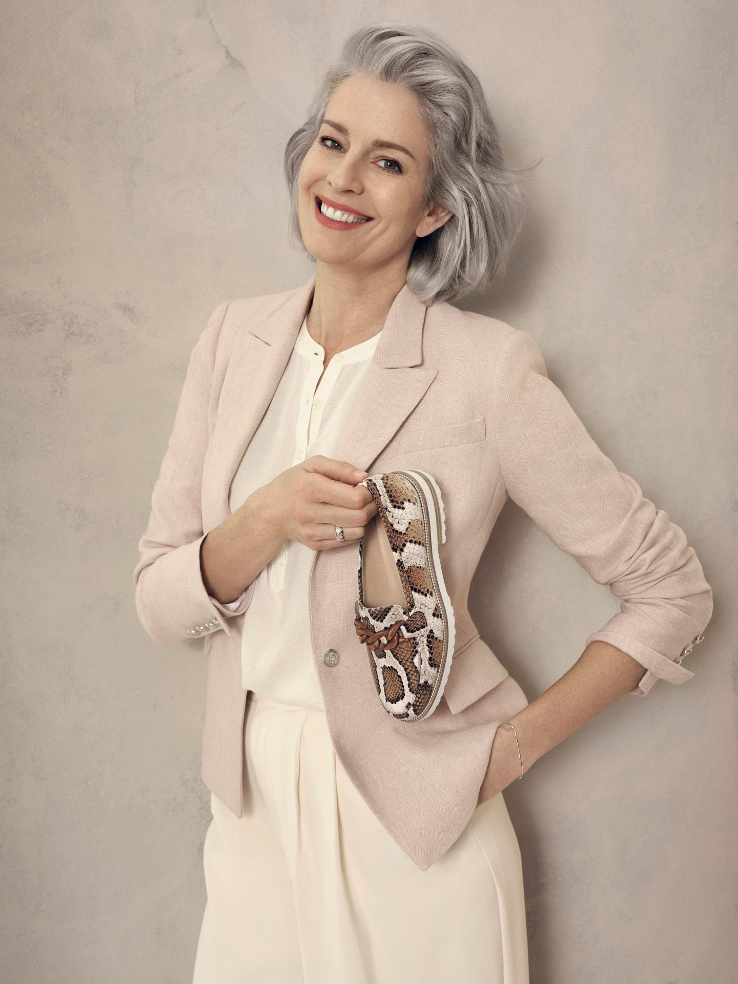 portrait of older woman smiling wearing white pants with white shirt and soft pink holding snake printed loafer for Jean-Paul Fortin summer-spring collection photographed by Maxyme G Delisle with artistic direction, conception and set design by Studio TB