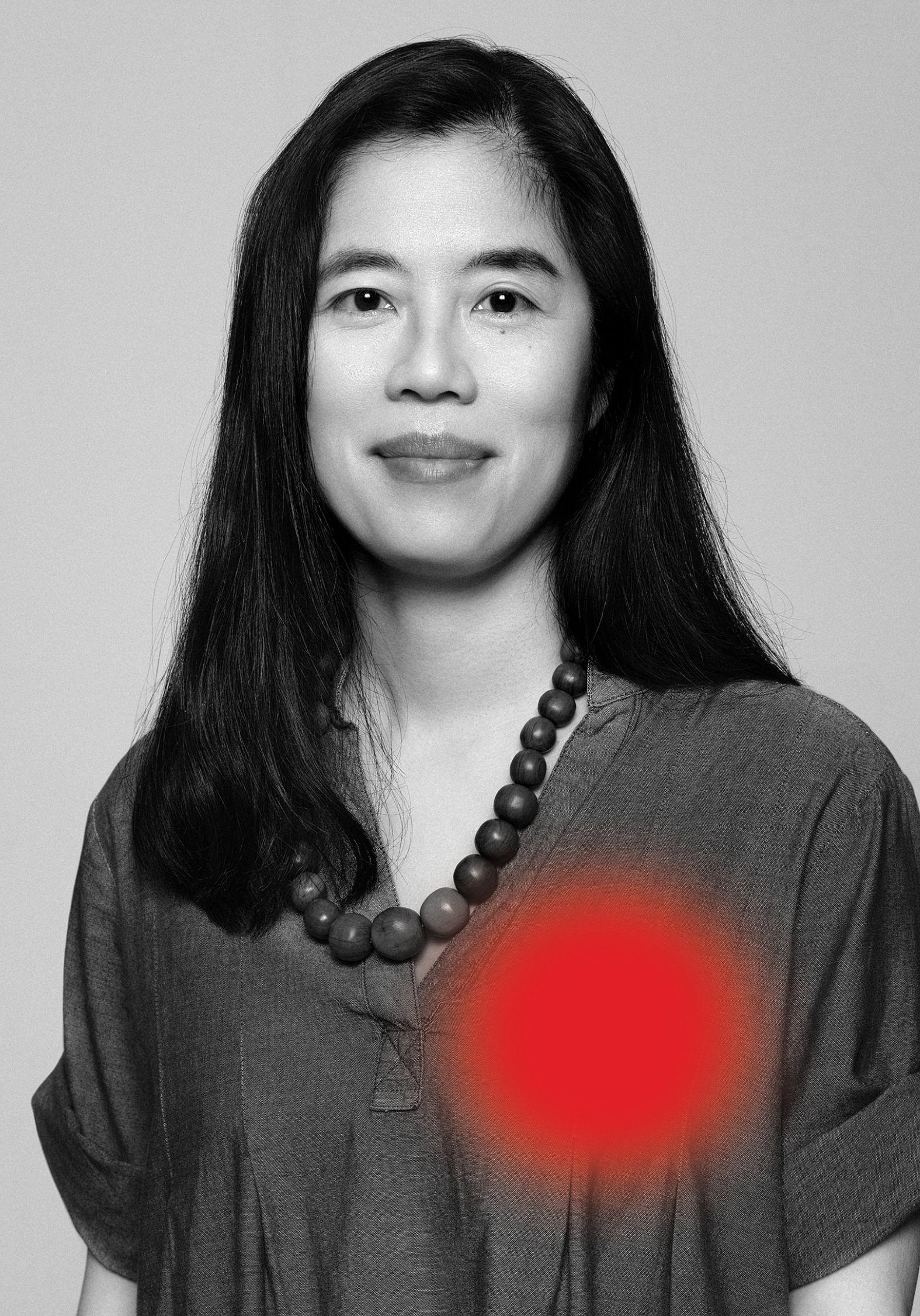 Portrait en noir et blanc de Karen Tam portant une chemise grise ample.