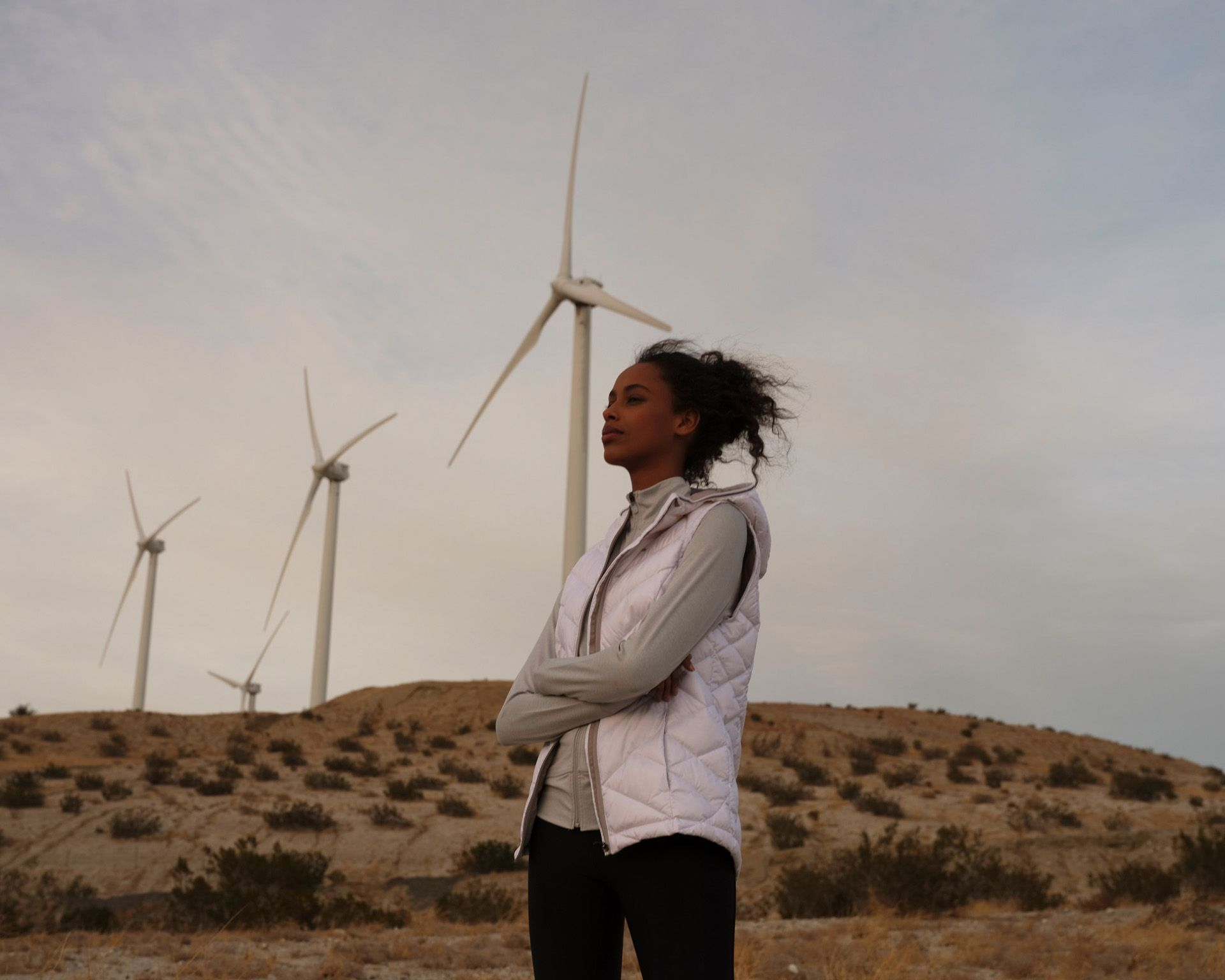 curly haired brunette female model walking in wind turbines field in Mexico at sunrise looking out to the horizon wearing pink puffy coat hair in the wind filmed by Les Gamins for Lole promotional video