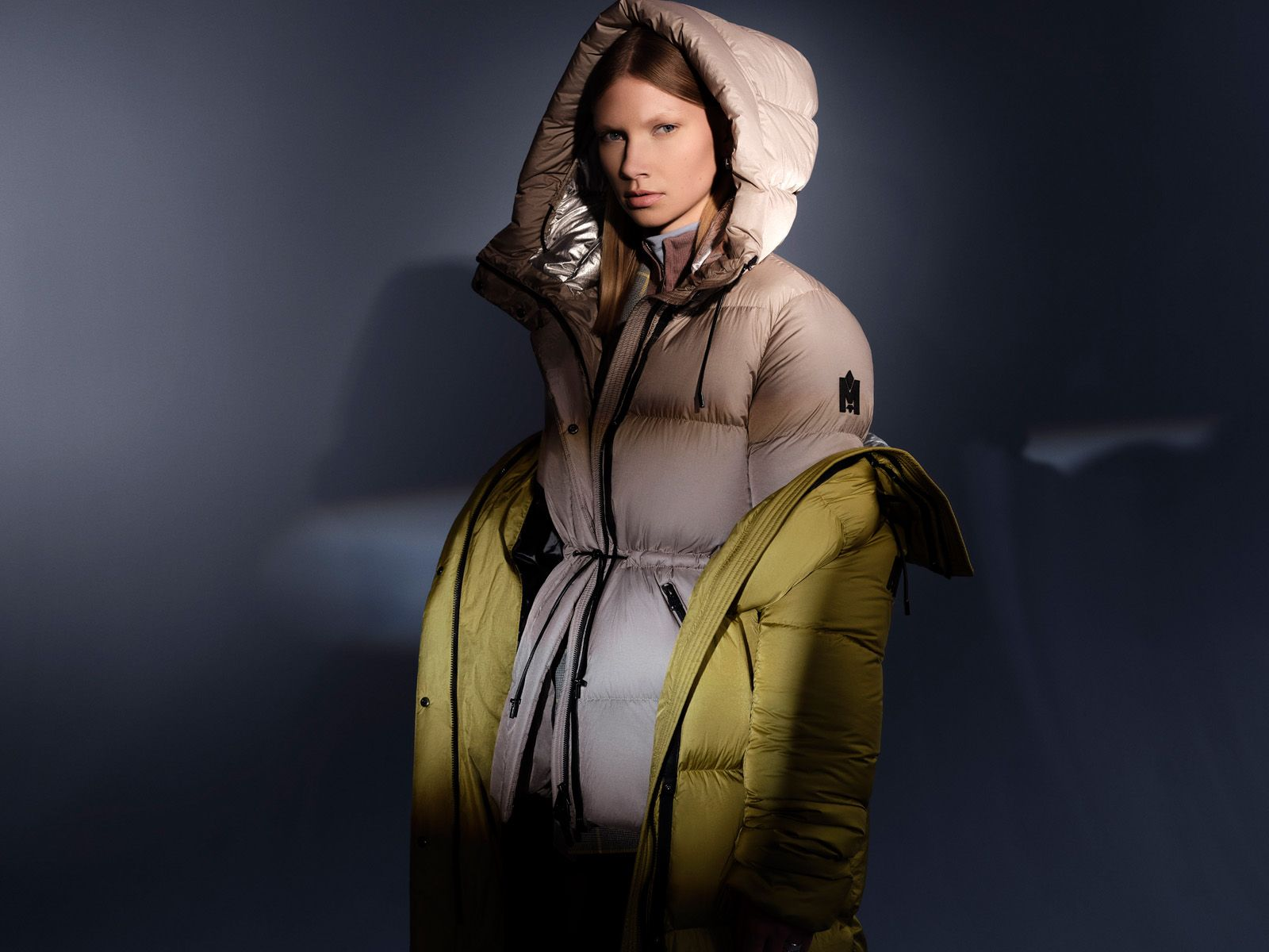 blonde model wearing beige winter coat with hood on and yellow winter coat on her arms on dark background looking at camera styled by Studio TB and photographed by Maxyme G. Delisle for Mackage