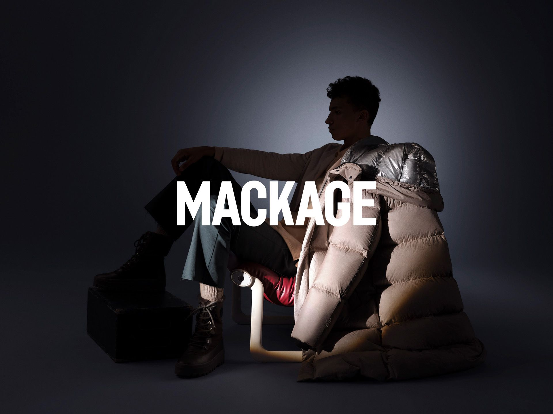 male model wearing beige winter coat sitting on designer chair on dark background head in the shadow styled by Studio TB and photographed by Maxyme G. Delisle for Mackage