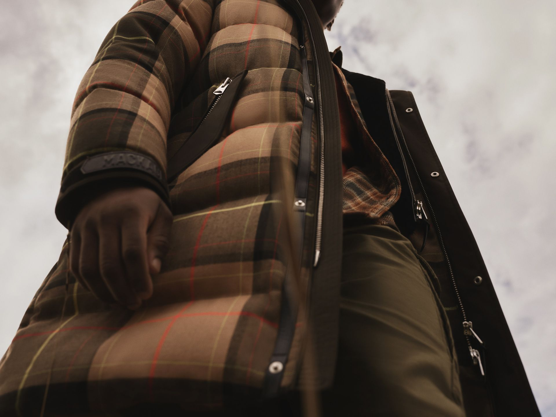 black male model wearing checkered winter coat in dry field close-up of hand photographed by Maxyme G Delisle for Mackage