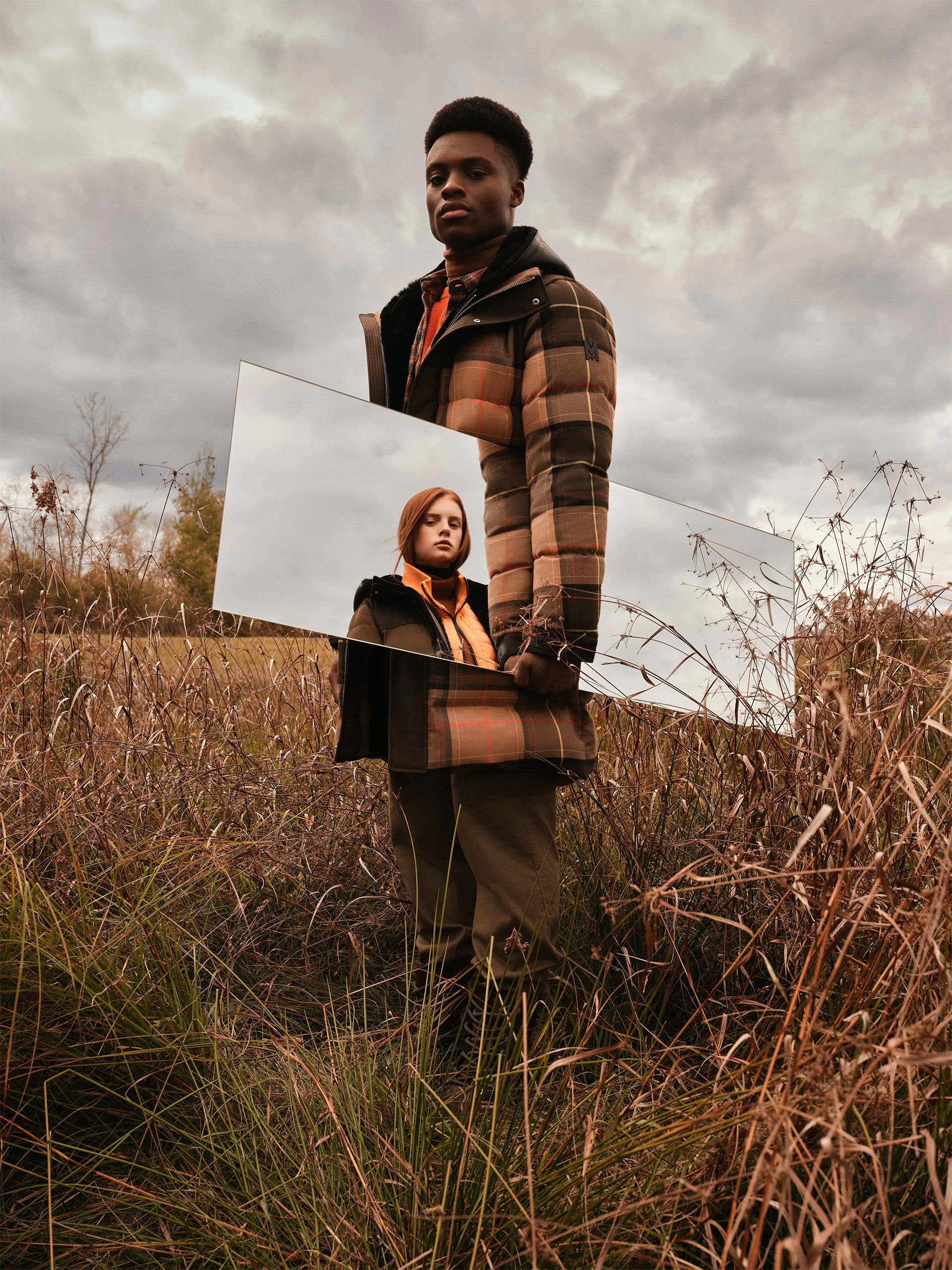 black model and ginger head model wearing coat reflection in mirror outside by Maxyme G Delisle for Mackage