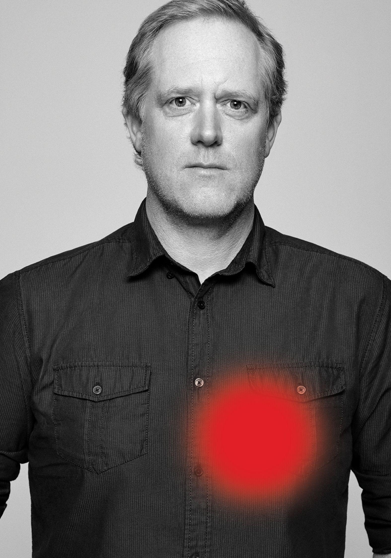 Portrait en noir et blanc de Marc Séguin portant une chemise rayée.