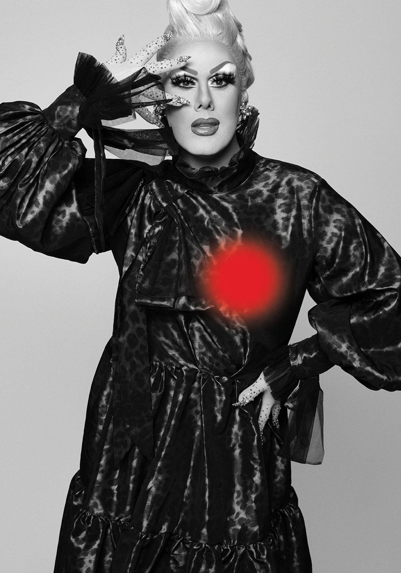 Portrait en noir et blanc de la drag queen Rita Baga portant une robe glamour et maquillée.