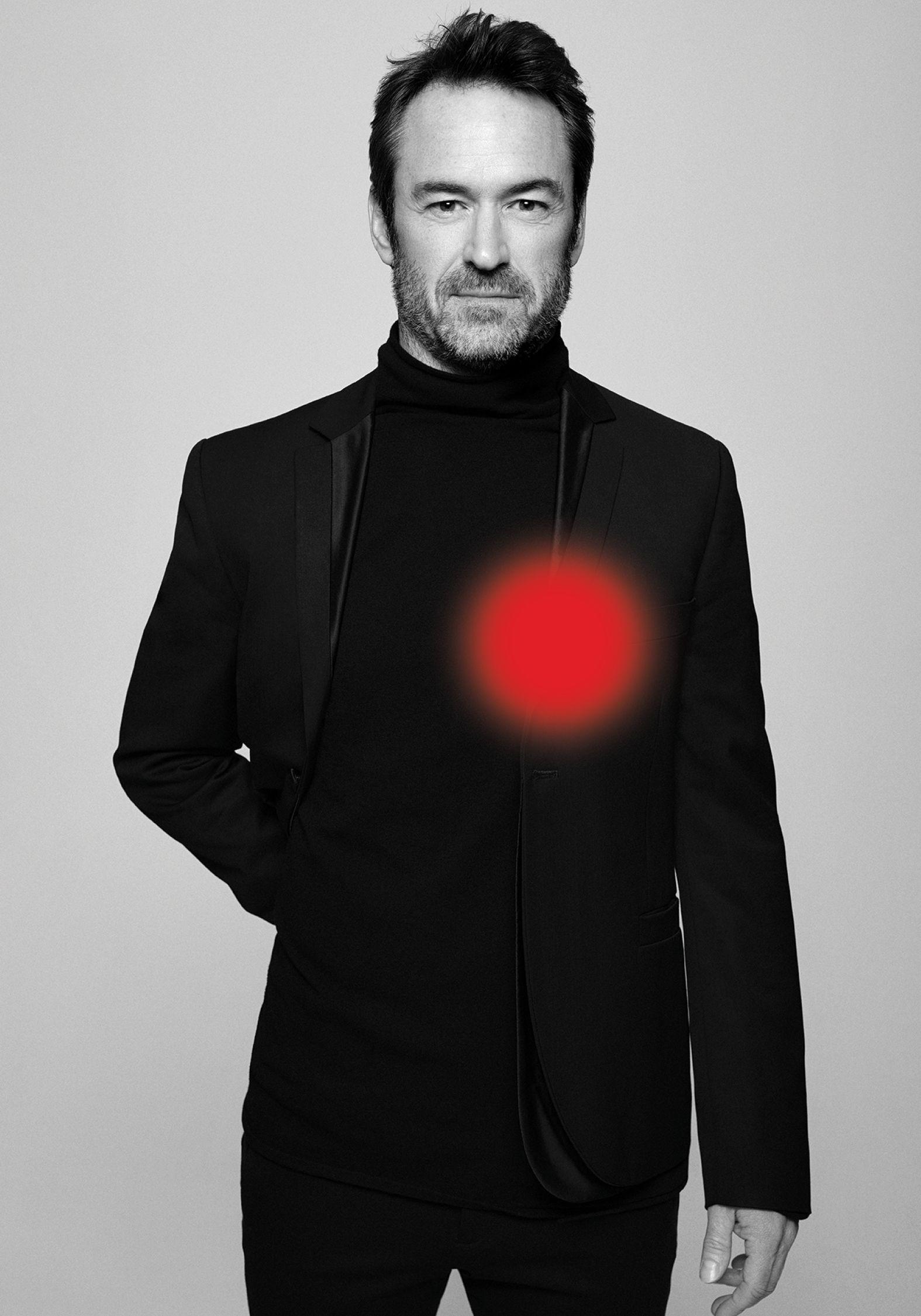 Portrait en noir et blanc de l'acteur Sébastien Ricard portant un costume noir et une main derrière le dos.