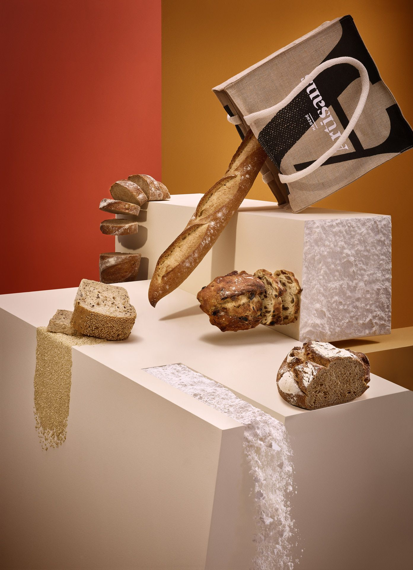 scenery showcasing different types and textures of breads flour baguettes seeds whole grain in orange ambiance by Mathieu Lévesque for Marché Artisans