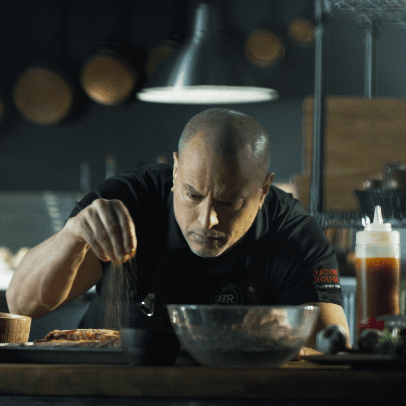 white man sprinkling spices on ribs in professional kitchen looking serious and focused by Mathieu Levesque for Baton Rouge