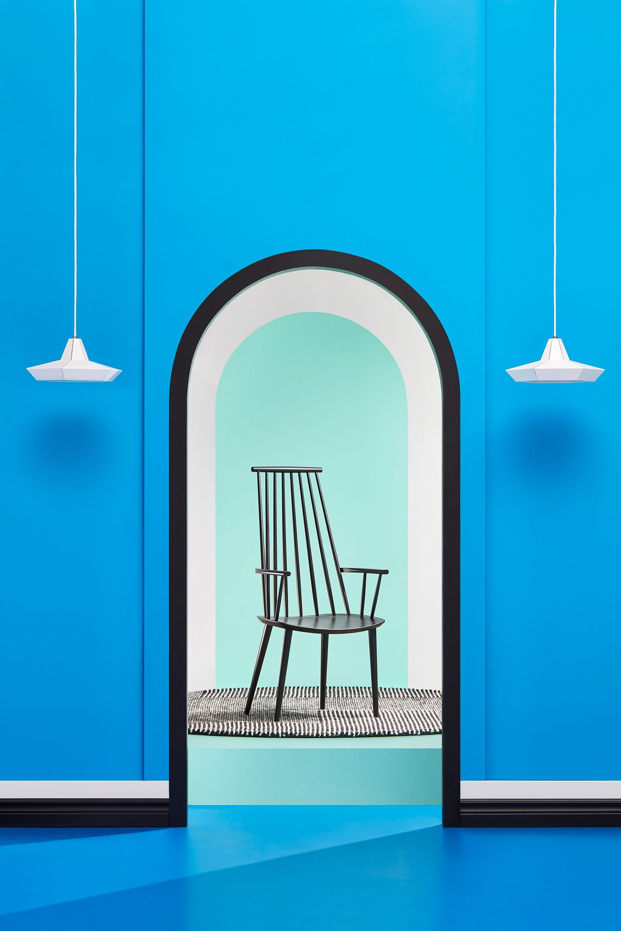 interior design with blue theme with black wide chair by Mathieu Levesque