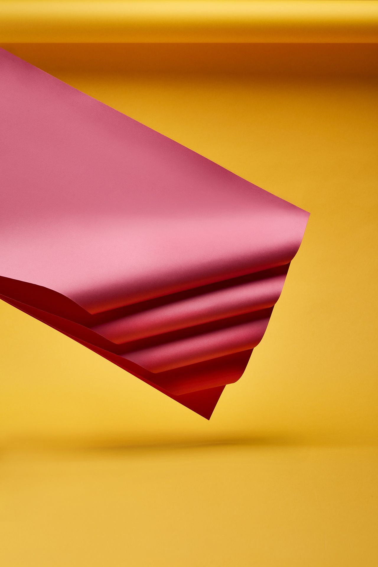 twisted and layered pink sheets of paper floating in the air on yellow background by Mathieu Levesque for enRoute