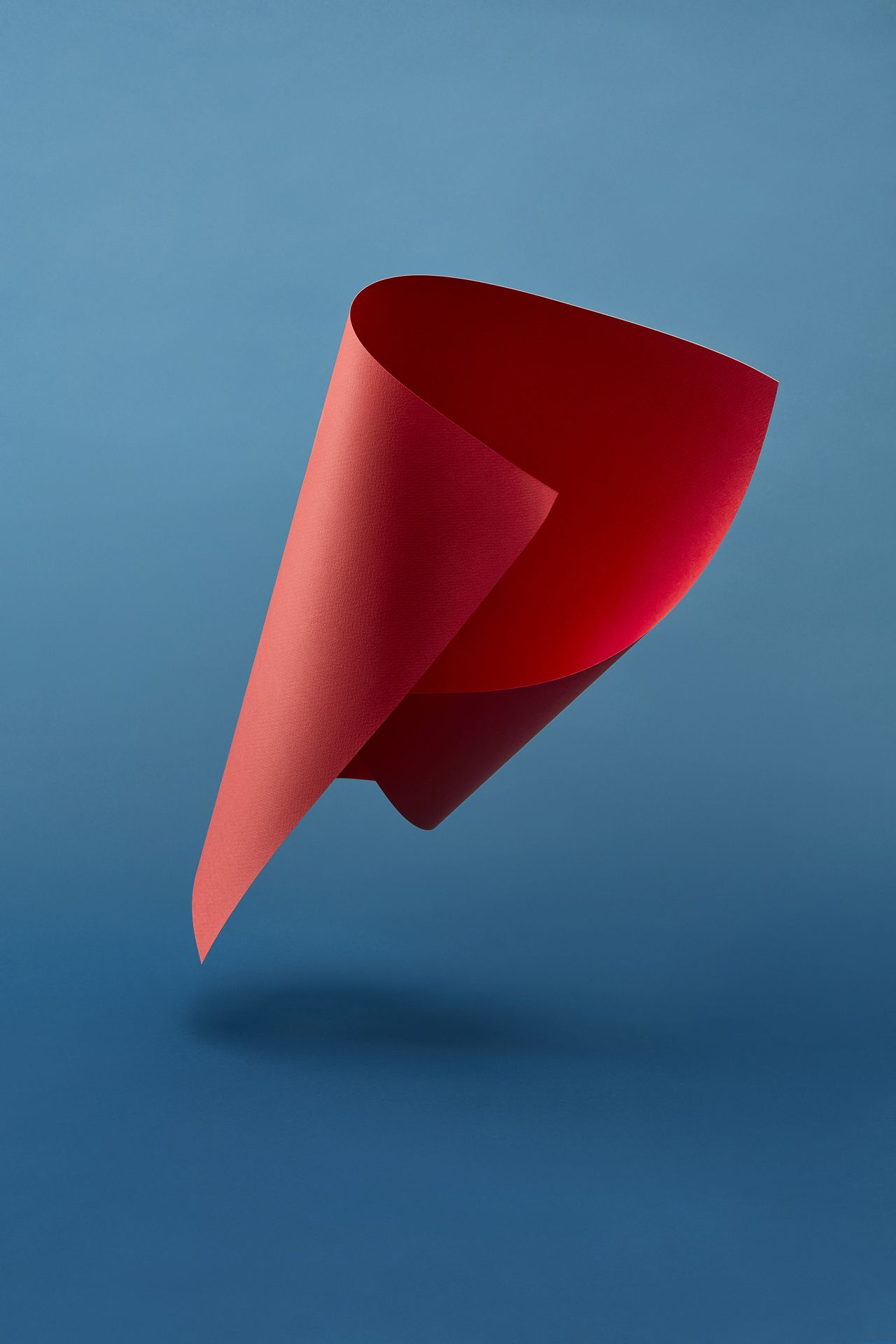 twisted sheet of red paper floating in the air on blue background by Mathieu Levesque for enRoute