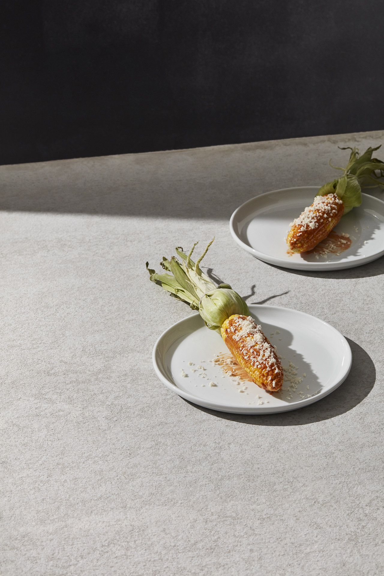 On a concrete table there are two white plates with cooked corn presented with sauce and grated cheese.