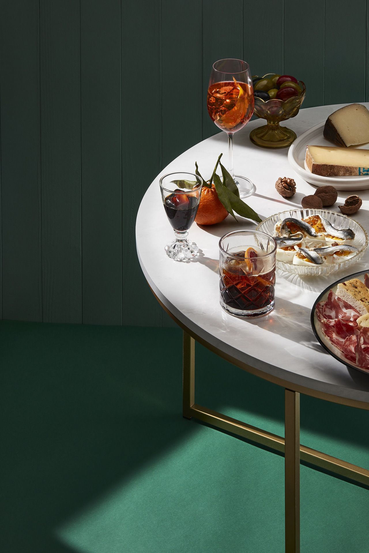 On top of an emerald green floor and background stands a marble table with gold legs. On the table there are olives in a cup, platters of cold cuts and cheeses and fancy cocktails.