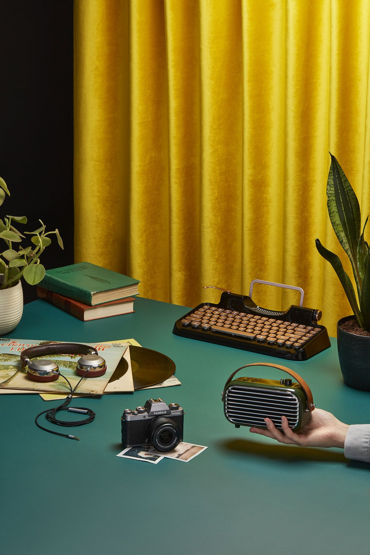 dark green table vintage radio typewriter vinyls argentic camera old books on top and yellow curtain in the background by Mathieu Levesque for enRoute Magazine Air Canada