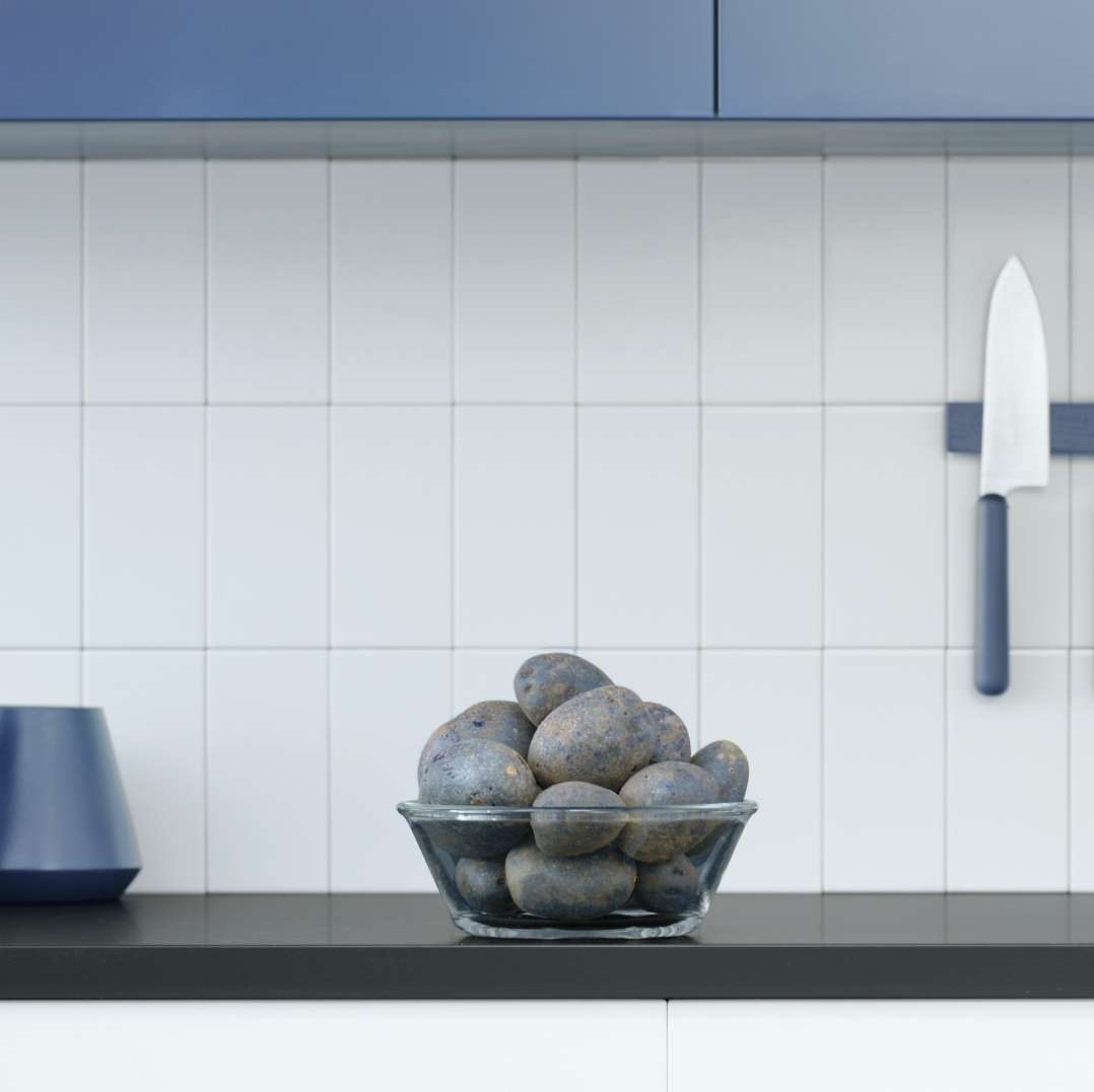 bowl of blue potatoes on grey countertops under blue cupboards in front of magnetic bleu knives by Mathieu Levesque