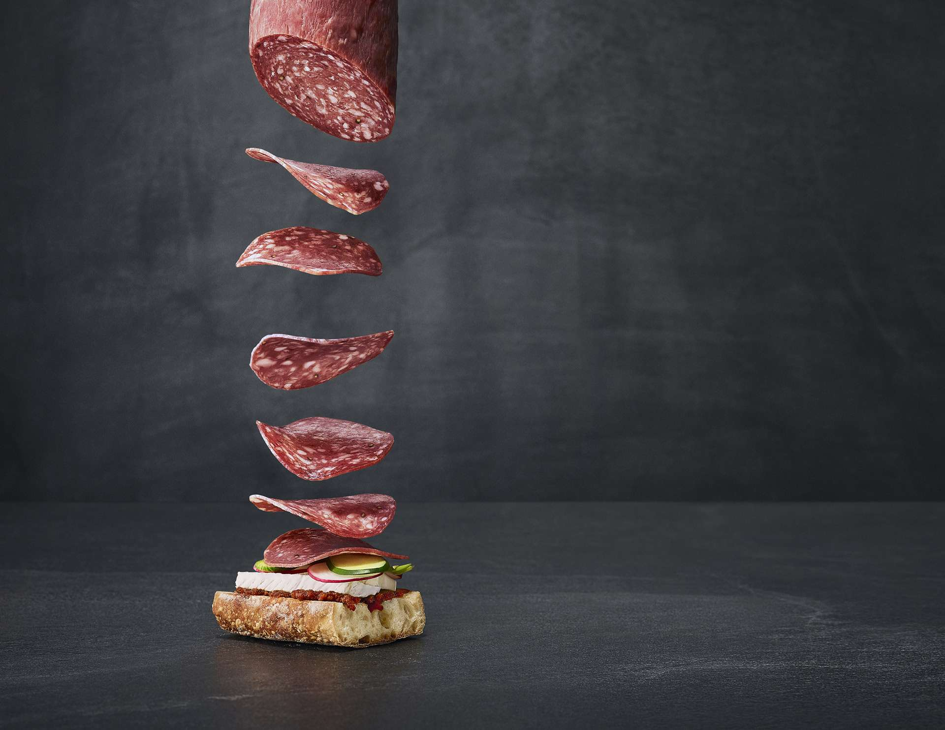 wide shot of salami slices falling softly on bread with tomato spread brie cheese and vegetables by Mathieu Levesque for Fantino and Mondello Rethink