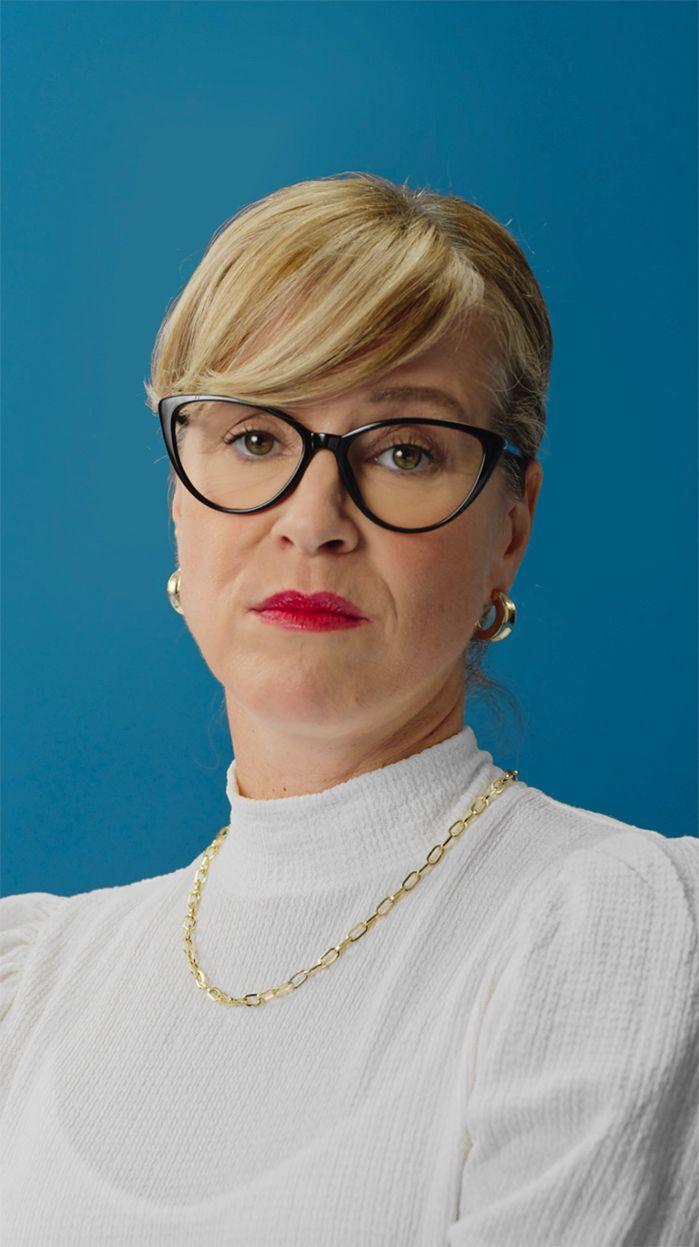 dame portant des lunettes et du rouge à lèvre devant un fond bleu