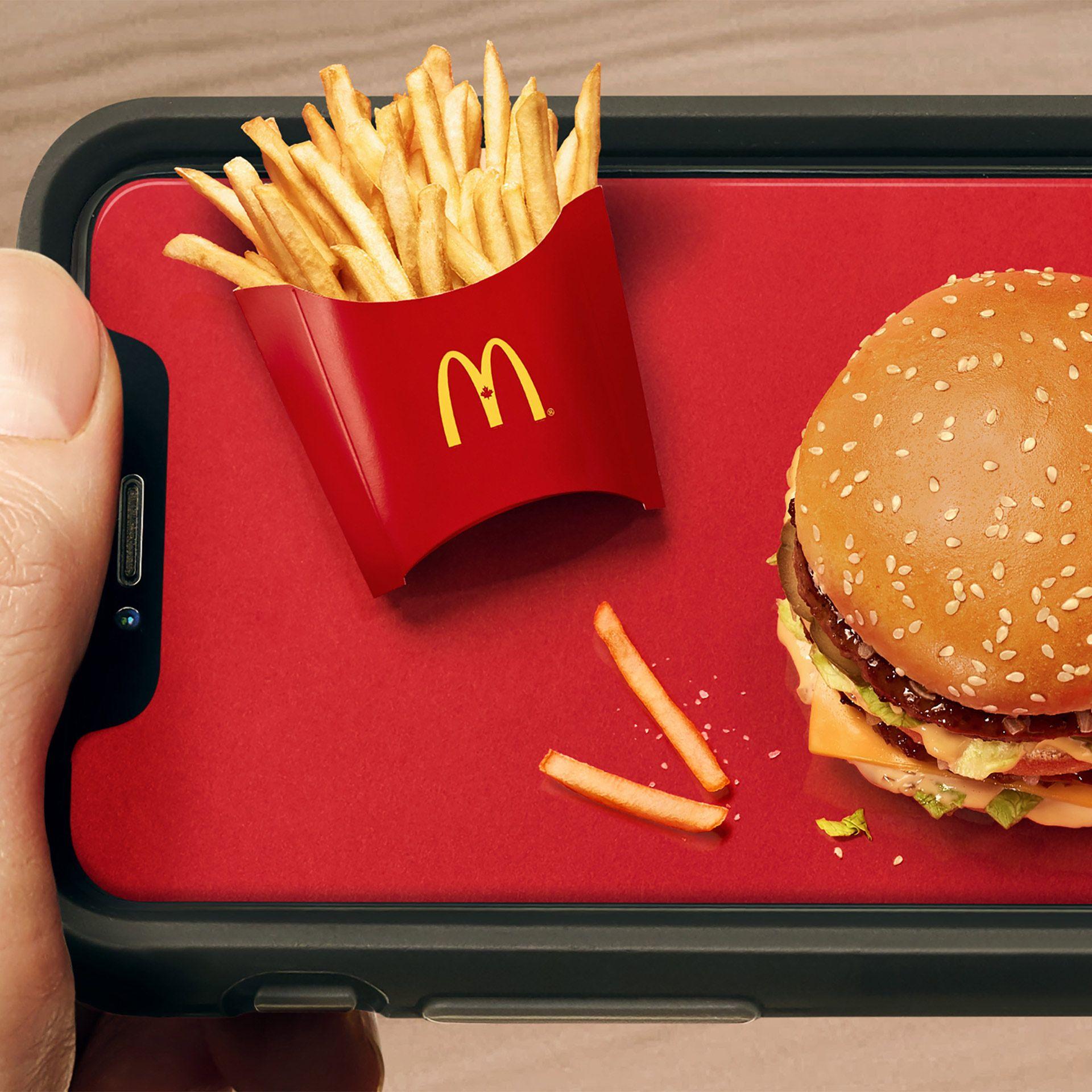 Gros plan de frites McDonald's miniatures placées sur un téléphone portable faisant office de plateau.