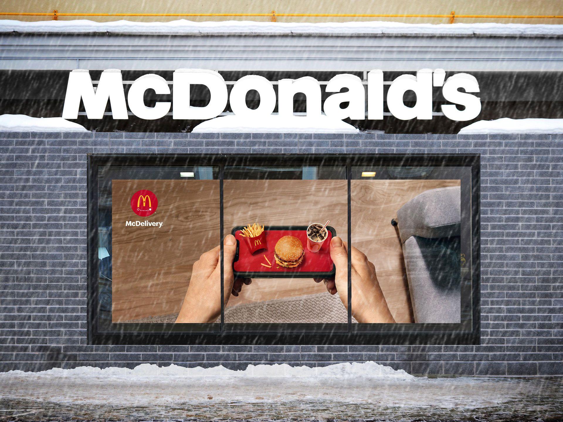 Scène d'hiver d'une fenêtre de McDonald's avec une affiche de l'image de la campagne à travers elle (des mains tenant un téléphone portable comme un plateau avec un trio dessus).
