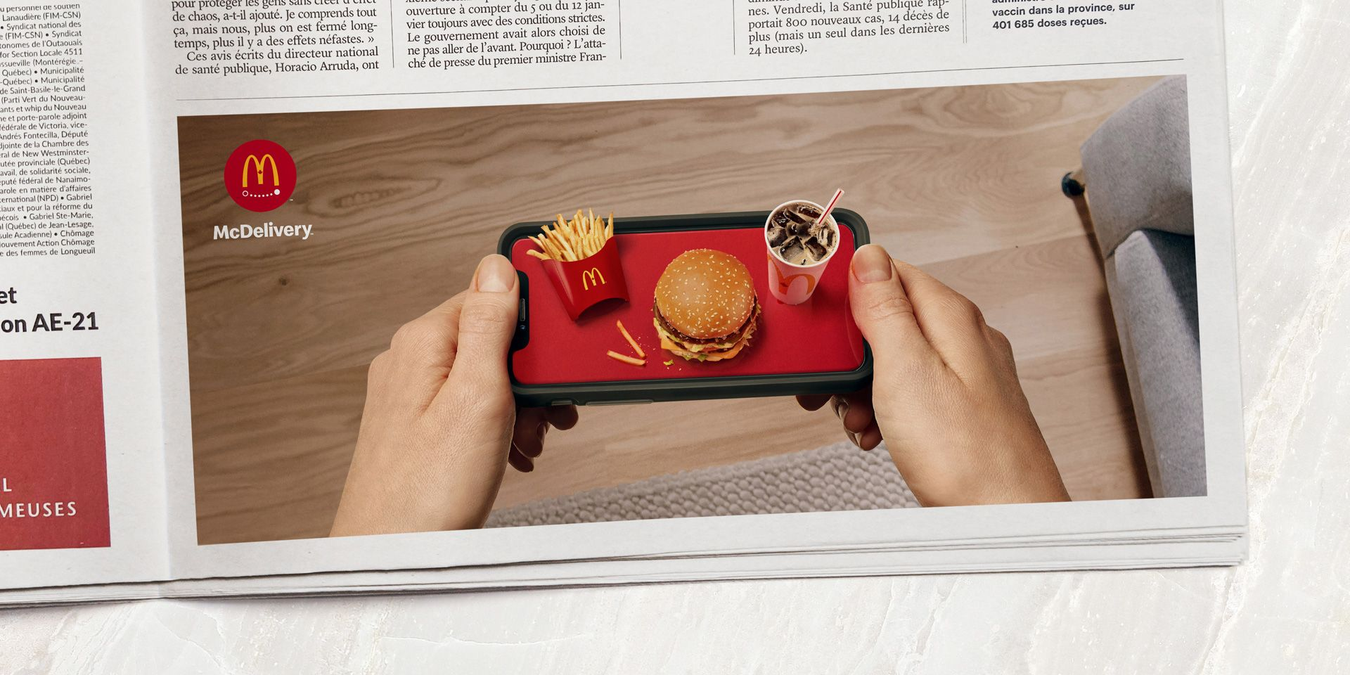 In a newspaper is a picture ad of two hands holding a tray which is a cellphone with a McDonald's trio on it.