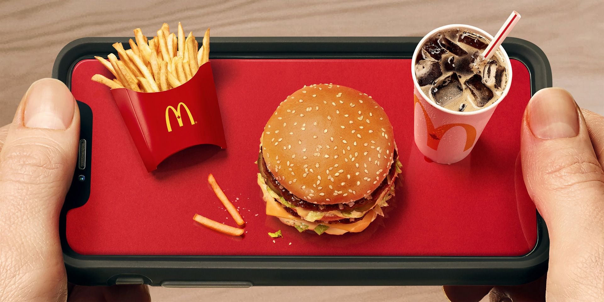 Gros plan de deux mains tenant un smartphone comme un plateau. L'écran du téléphone portable est rouge et sur celui-ci figure un trio McDonald miniature.