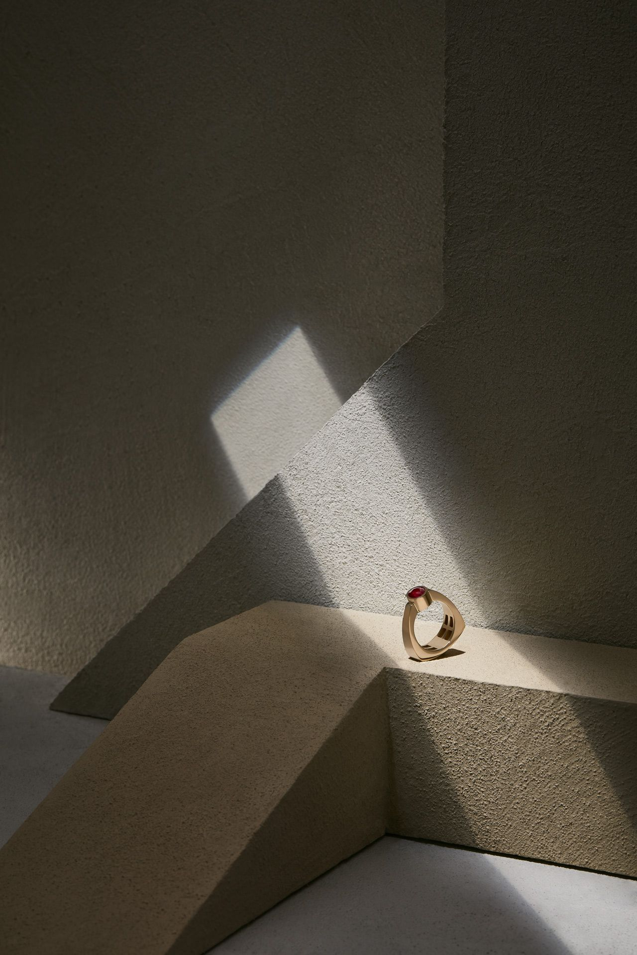 gold ring with red diamond placed in ray of light in cave or vault-like setting by Mathieu Levesque for Morrier jewelry