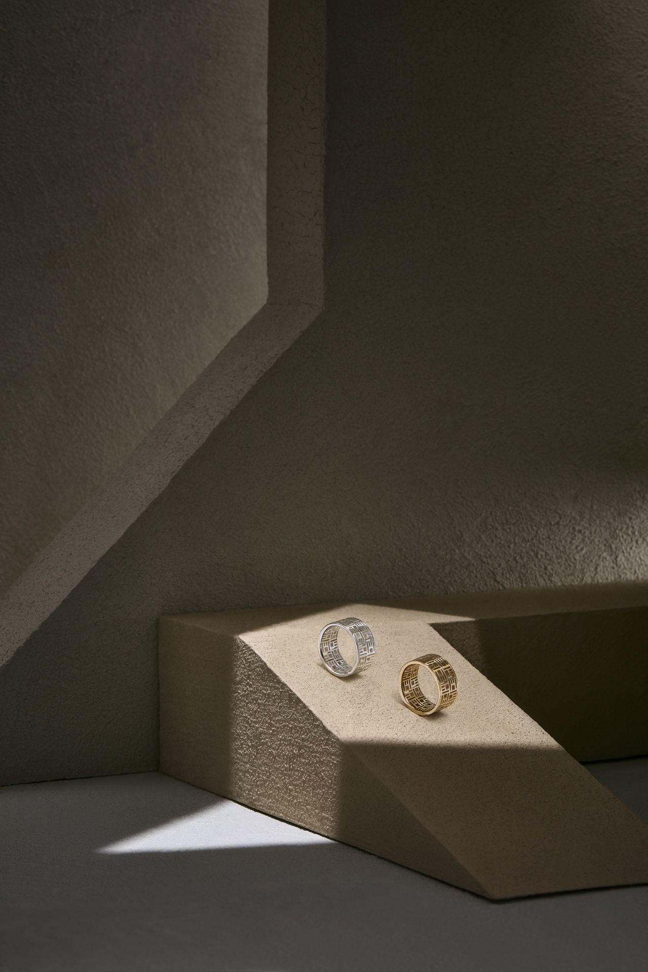 gold and silver carved ring in ray of light in cave or vault-like setting by Mathieu Levesque for Morrier jewelry