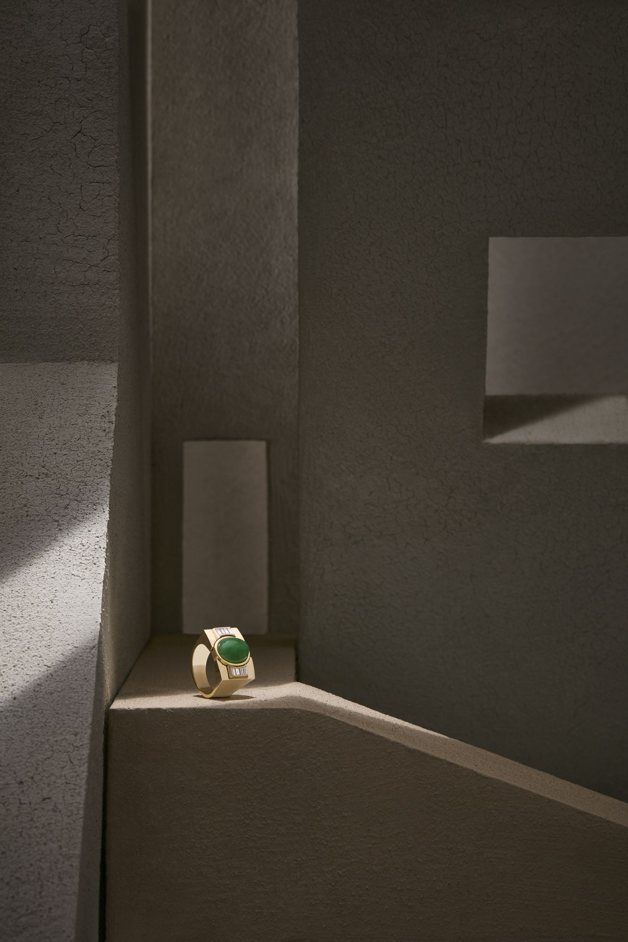 gold ring with green stone and white diamond placed in ray of light in cave or vault-like setting by Mathieu Levesque for Morrier jewelry