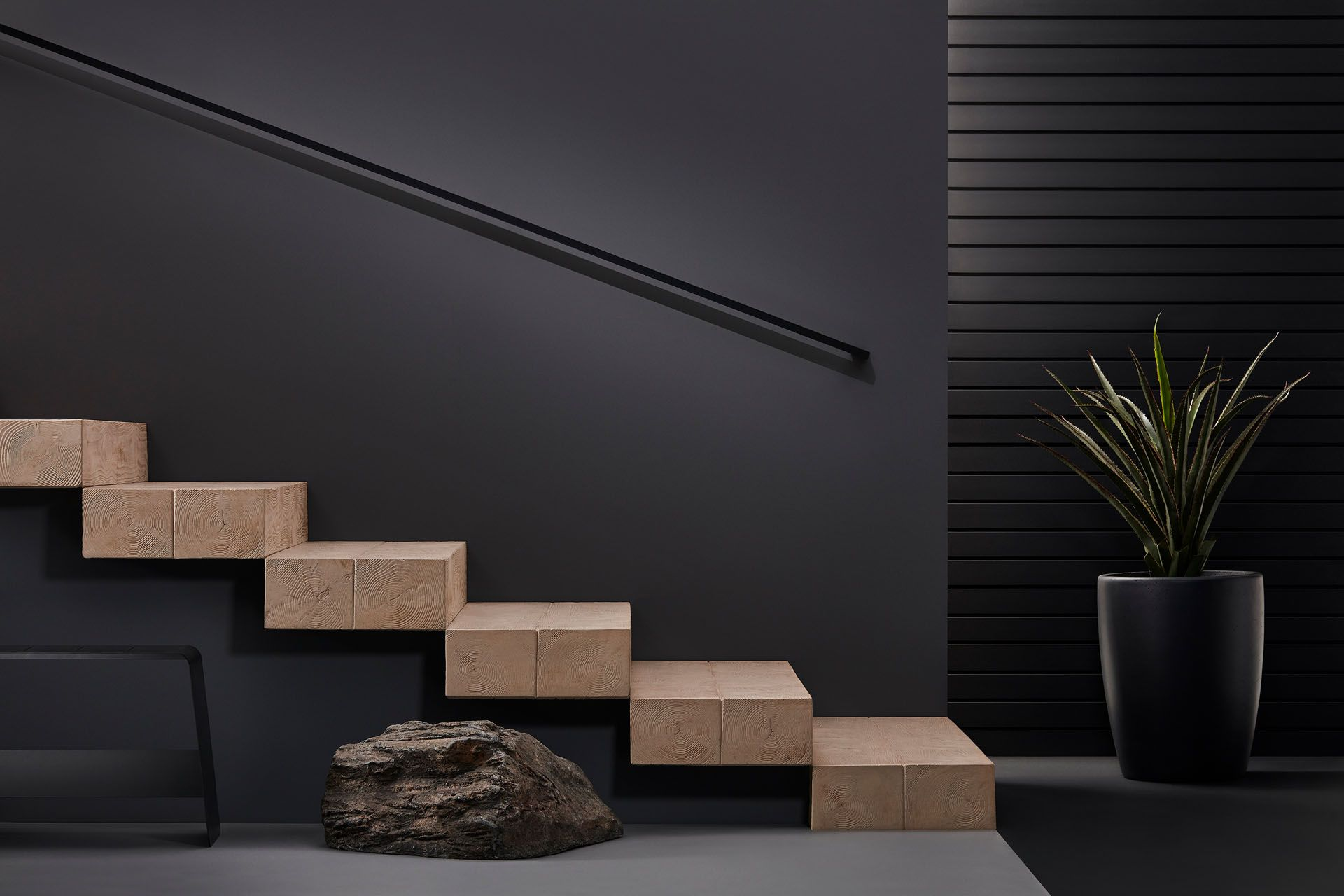 wooden stairs beside rock and potted plant by Mathieu Levesque for Techo Bloc