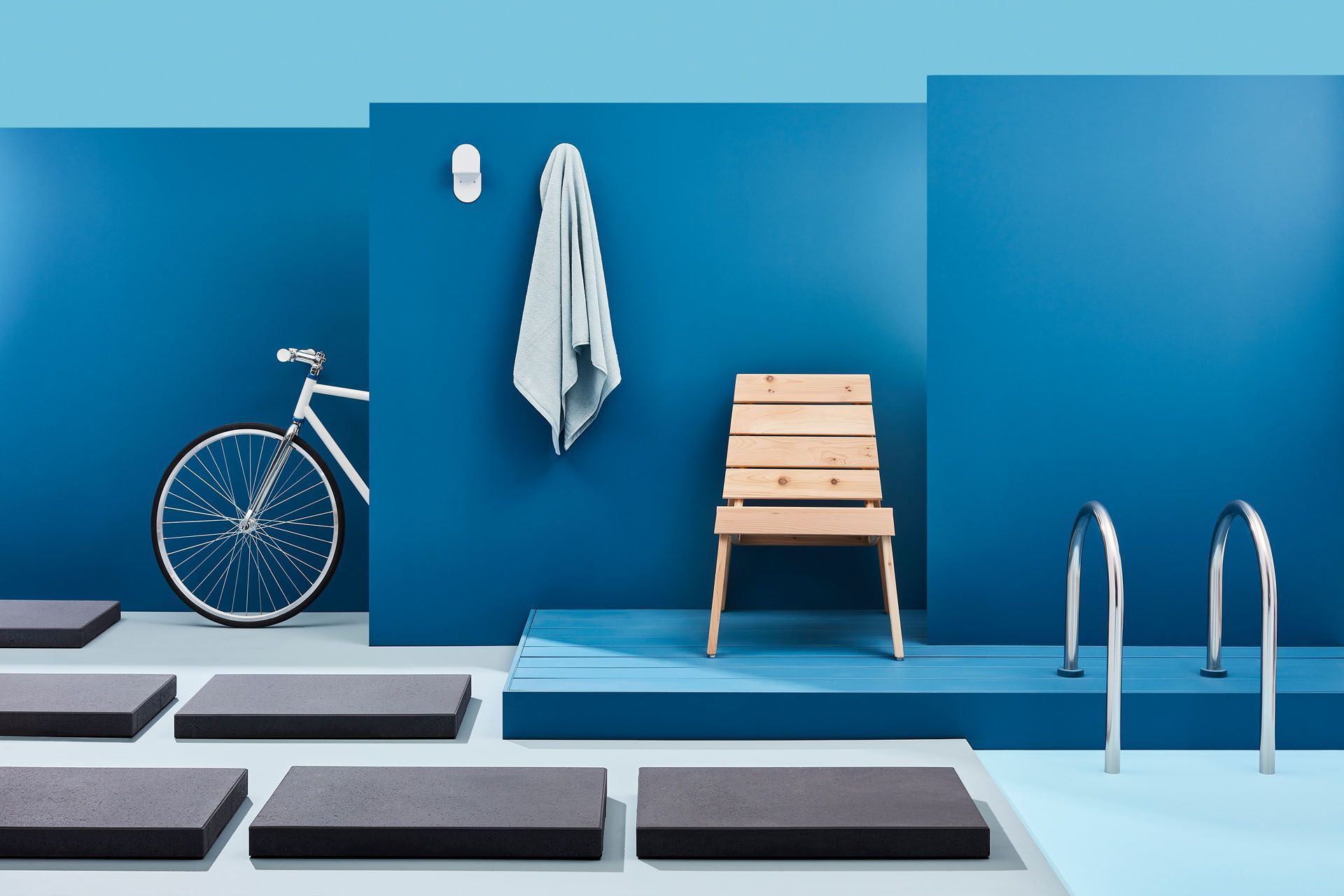 wooden chair on blue background at pool side by Mathieu Levesque for Techo Bloc