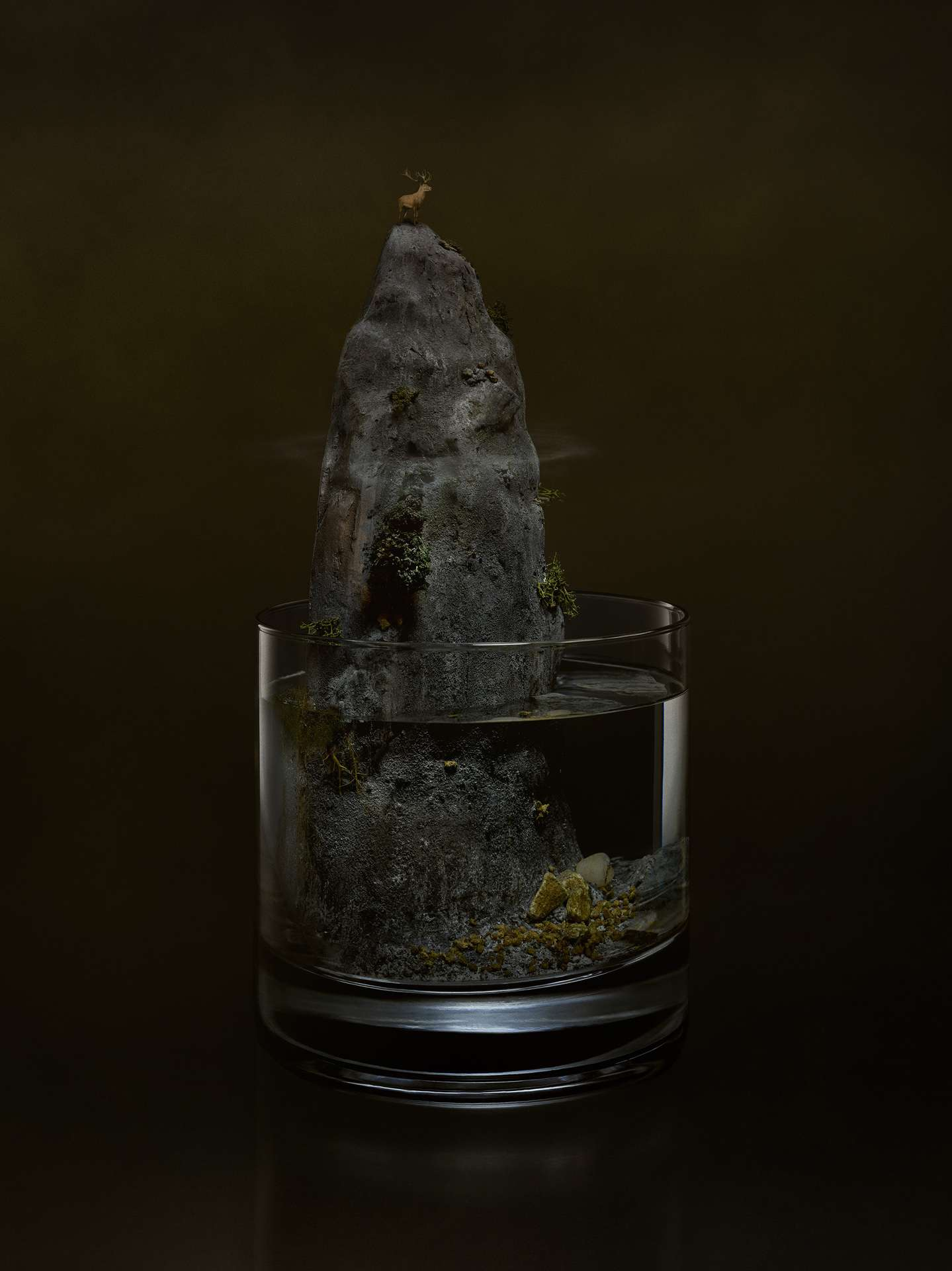 glass of alcohol with miniature scenery of tall grey rock with deer at the top on dark brown background by Mathieu Levesque