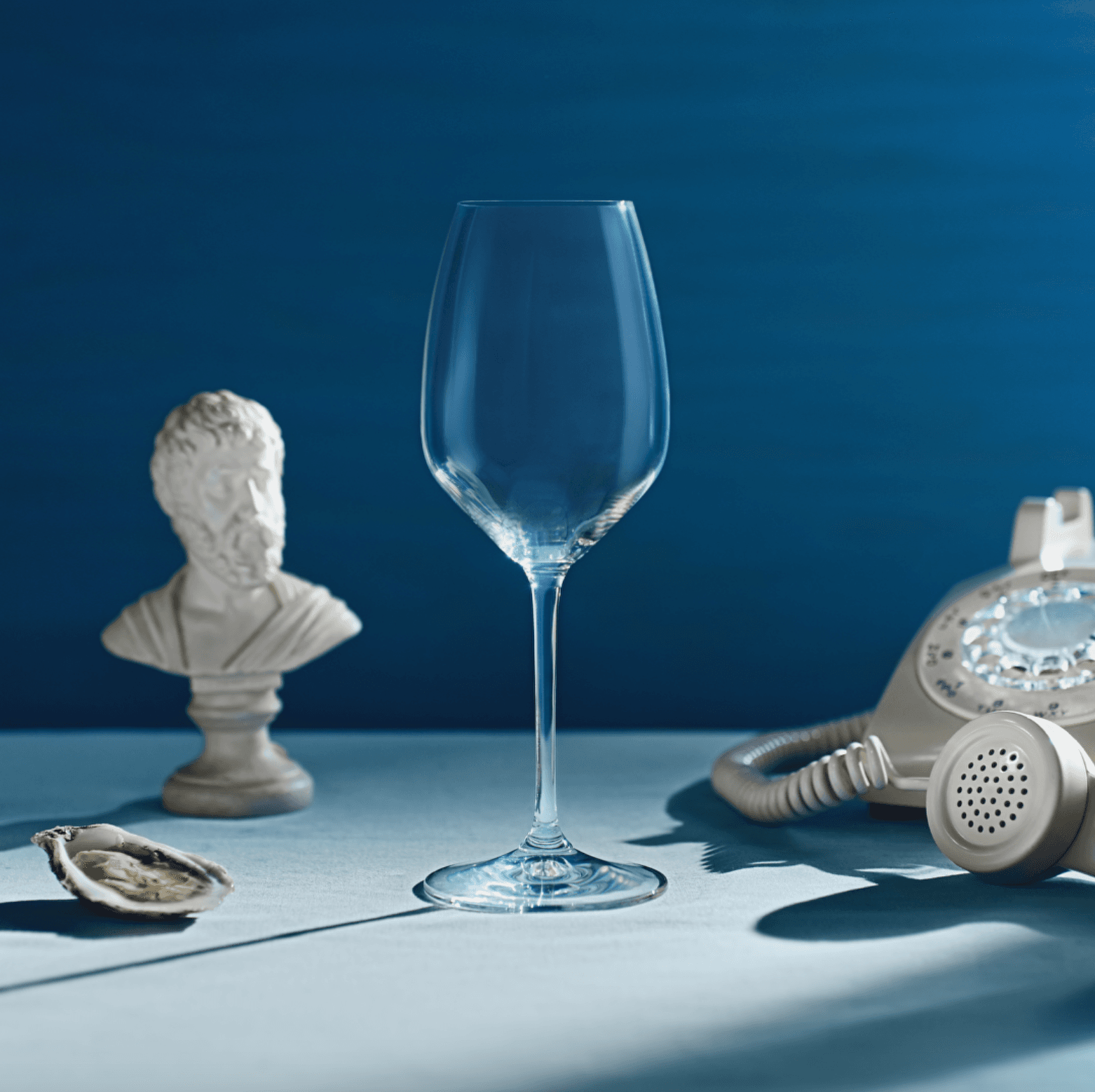Wine glass in the light on a blue surface and with a blue background. A grecque bust sculpted is behind, a vintage beige phone and an opened oyster.