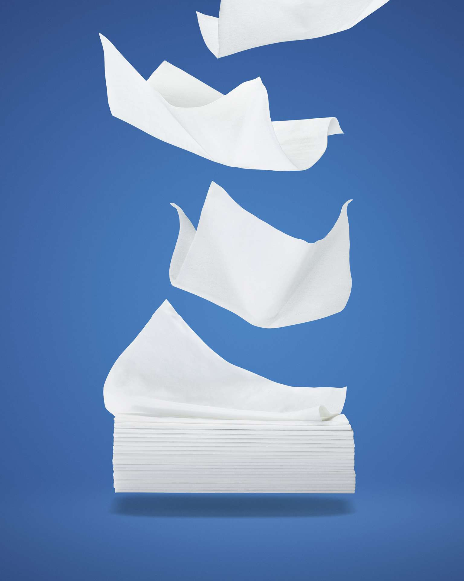 white tissues falling from the sky forming the shape of a box on blue background by Mathieu Lévesque for Uniprix