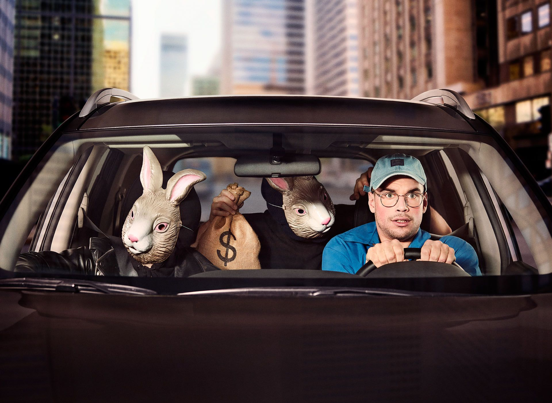 young male driving a car scared two thieves in the car wearing bunny masks holding guns and bags of money by Jocelyn Michel for Netlift