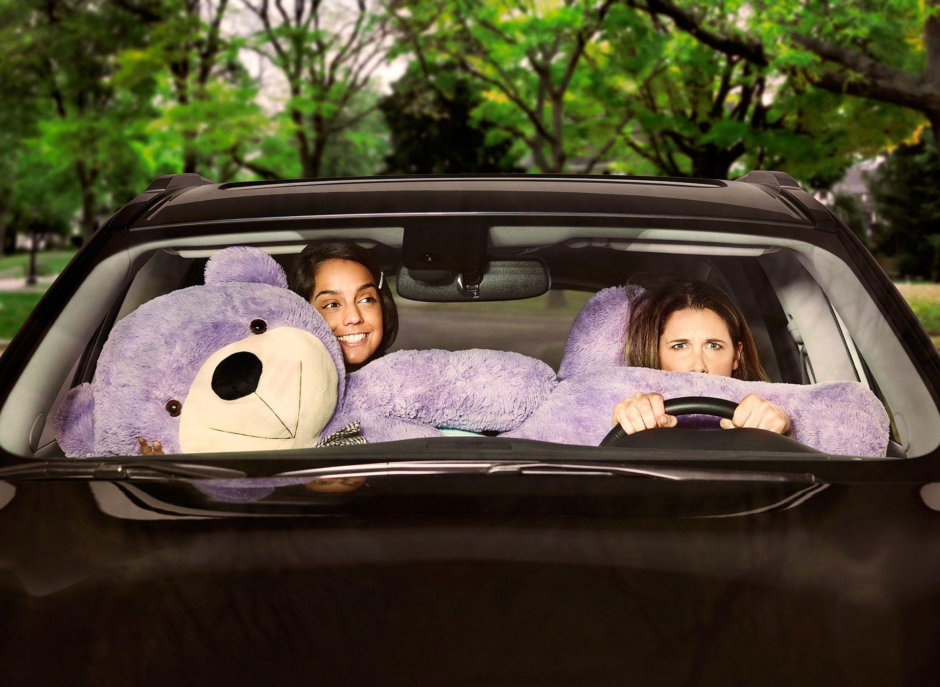 Deux filles en voiture avec un ours en peluche mauve géant prenant toute la place et énervant la conductrice par Jocelyn Michel pour Netlift