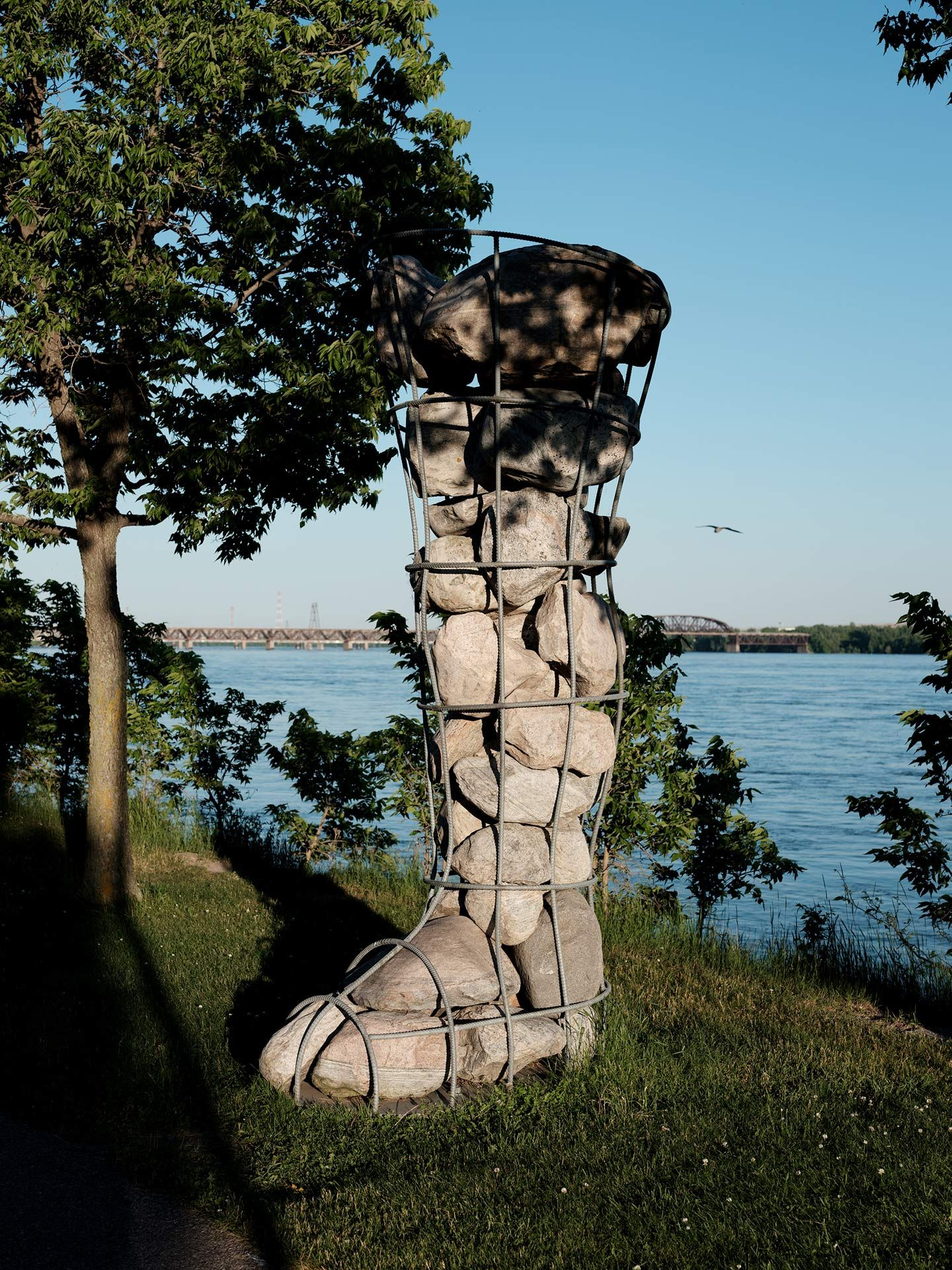 sculpture of boot made of metal wire filled with rocks next to a lake by Guillaume Simoneau