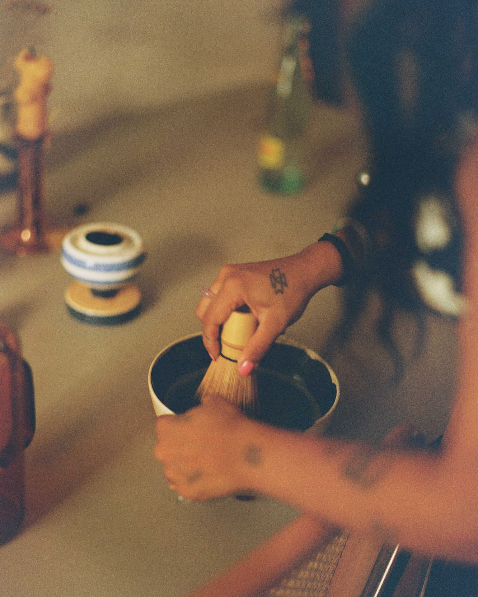 close up of writer Fariha Roisin whipping up matcha in a bowl photographed by Oumayma B. Tanfous for Levi's