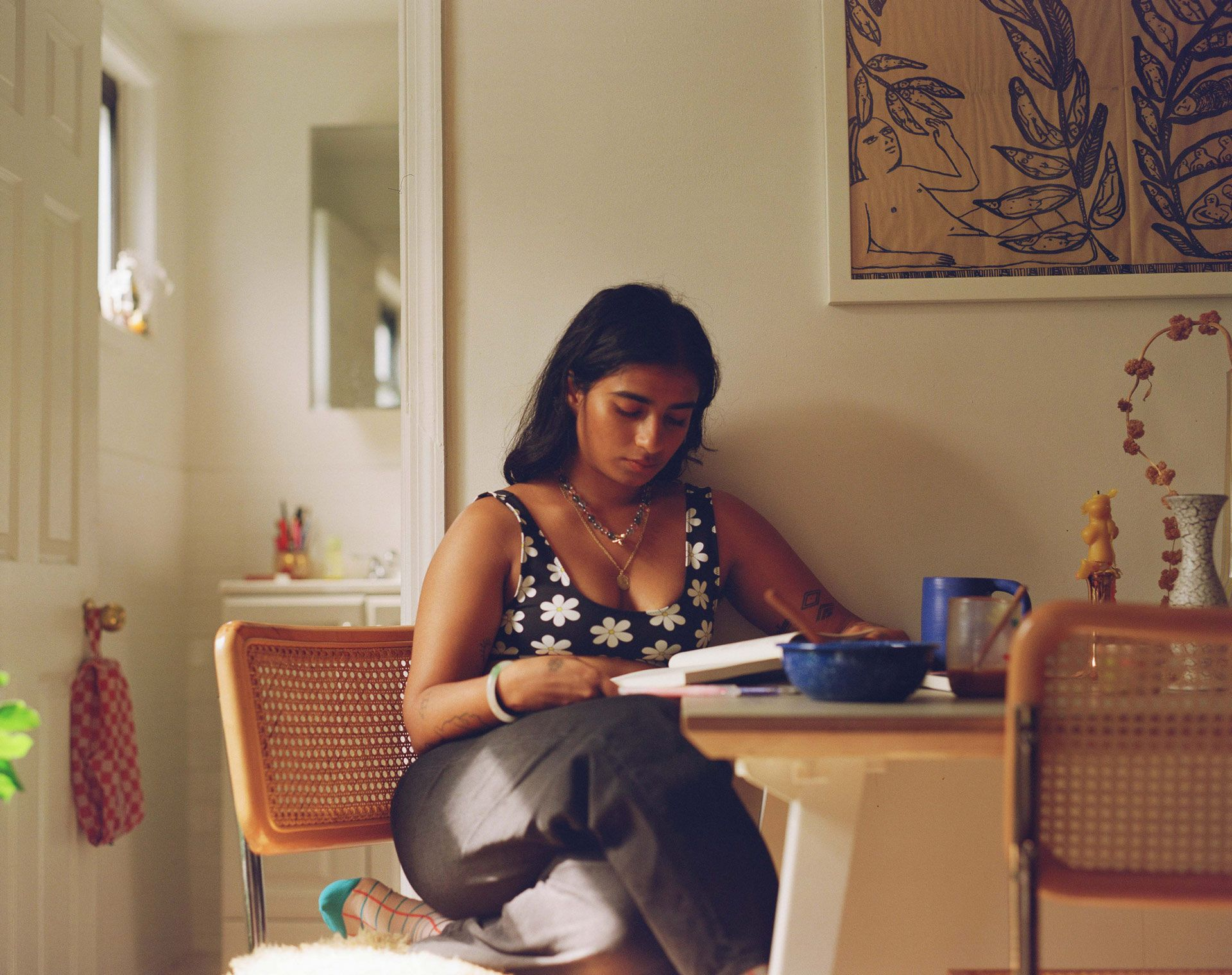 writer Fariha Roisin sitting at her kitchen table while reading wearing black jeans and flower-patterned sports bra photographed by Oumayma B. Tanfous for Levi's