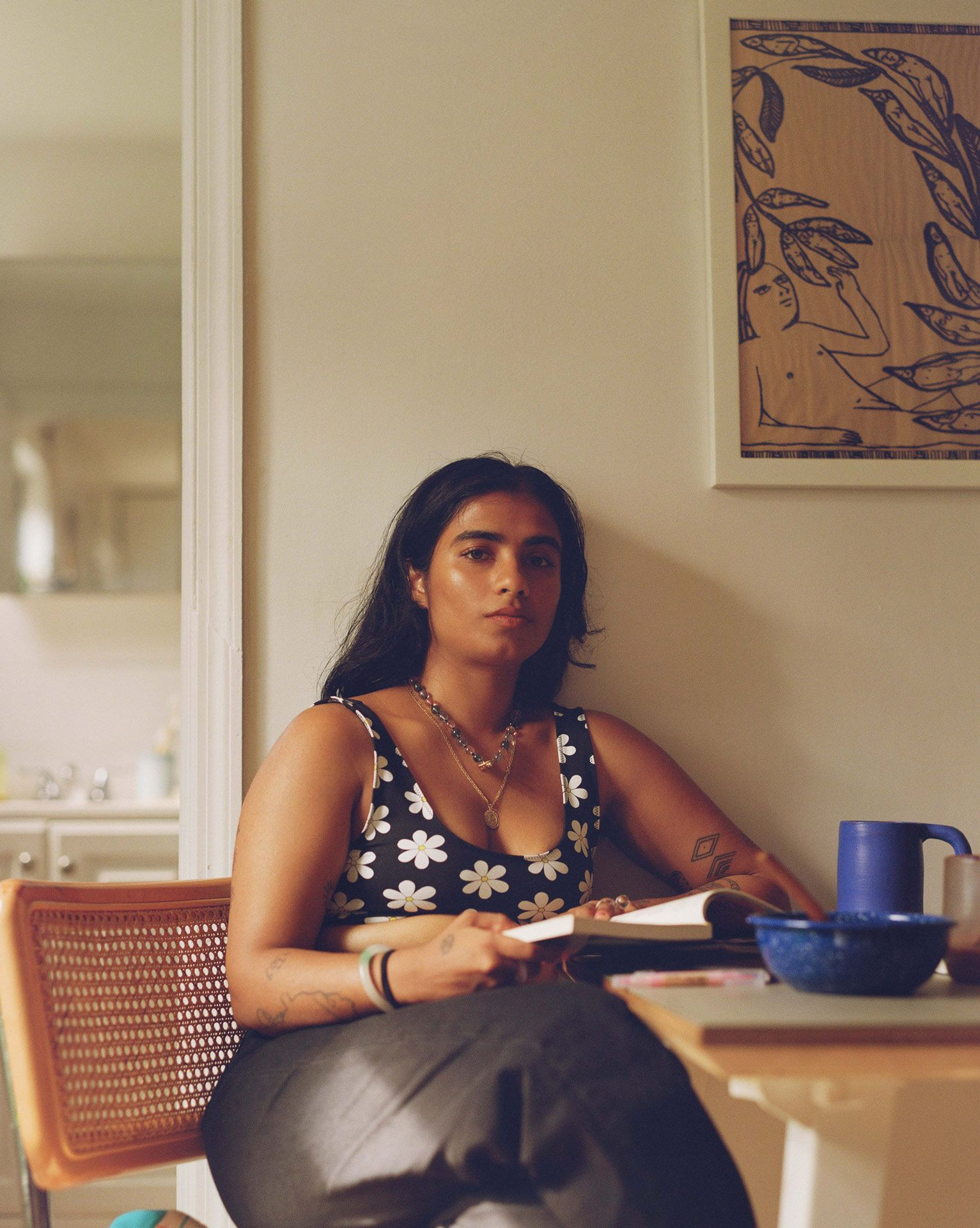 writer Fariha Roisin sitting at her kitchen table looking at camera and holding a book wearing black jeans and flower-patterned sports bra photographed by Oumayma B. Tanfous for Levi's