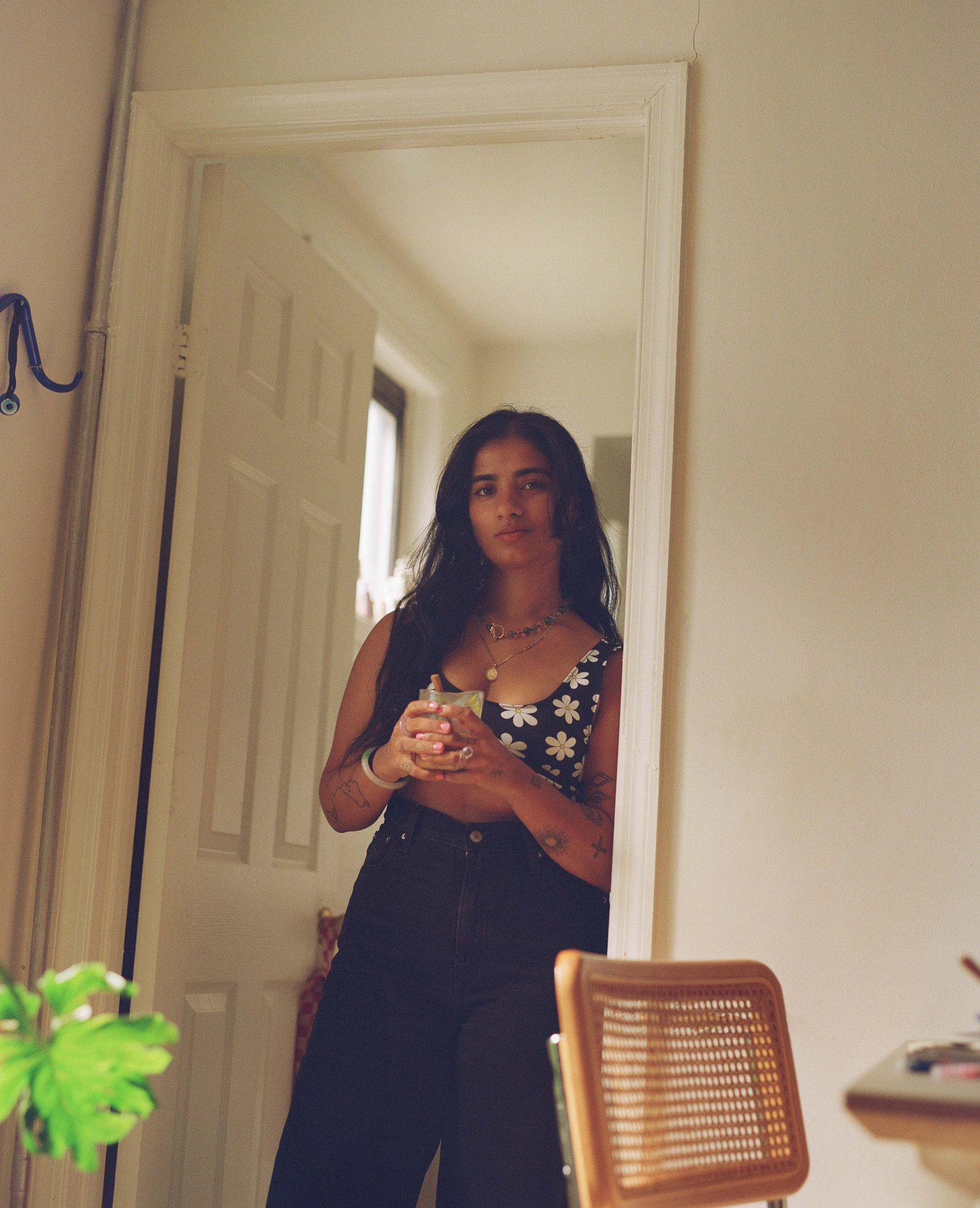 writer Fariha Roisin standing in her kitchen doorframe smiling and looking at camera holding teacup photographed by Oumayma B. Tanfous for Levi's