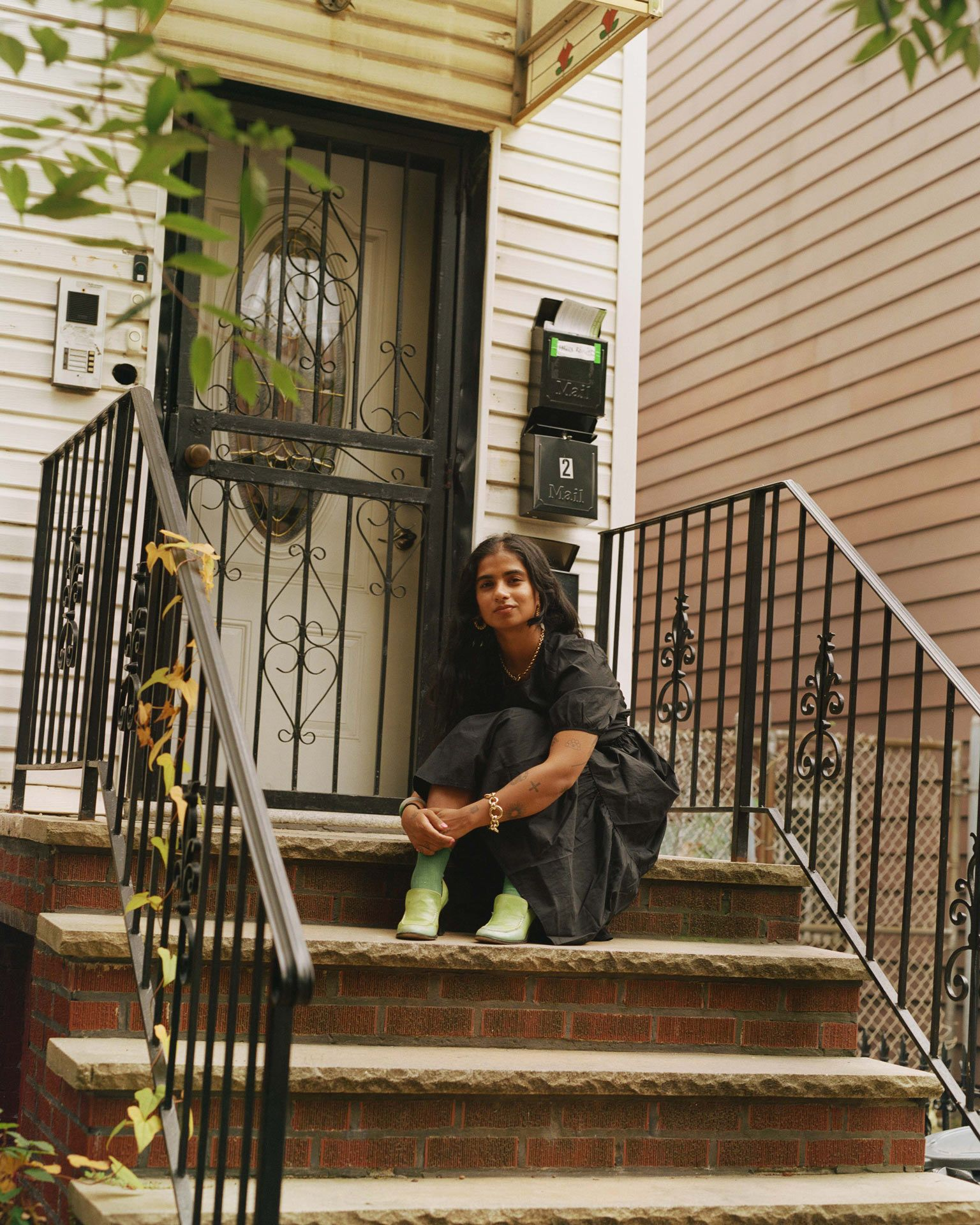 writer Fariha Roisin sitting on the stairs in front of her apartment wearing black dress green socks and green shoes looking at camera smiling with her arms around her knees photographed by Oumayma B. Tanfous for Levi's