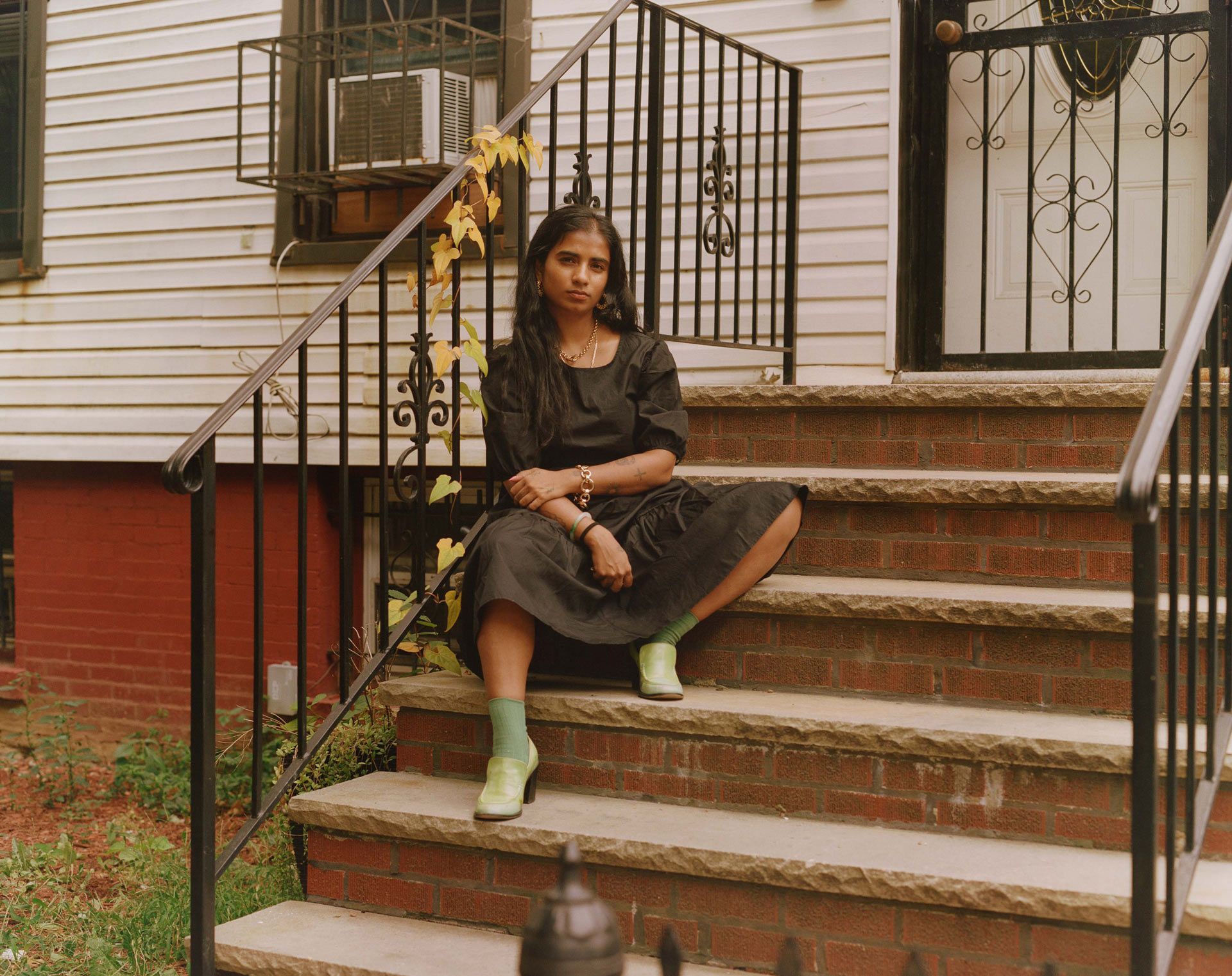 writer Fariha Roisin sitting on the stairs in front of her apartment wearing black dress green socks and green shoes looking at camera photographed by Oumayma B. Tanfous for Levi's
