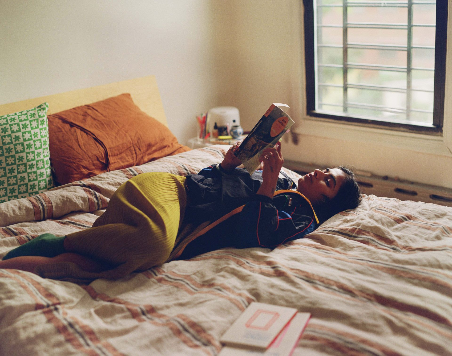writer Fariha Roisin laying and reading in her bed wearing yellow pants and dark blue bomber photographed by Oumayma B. Tanfous for Levi's