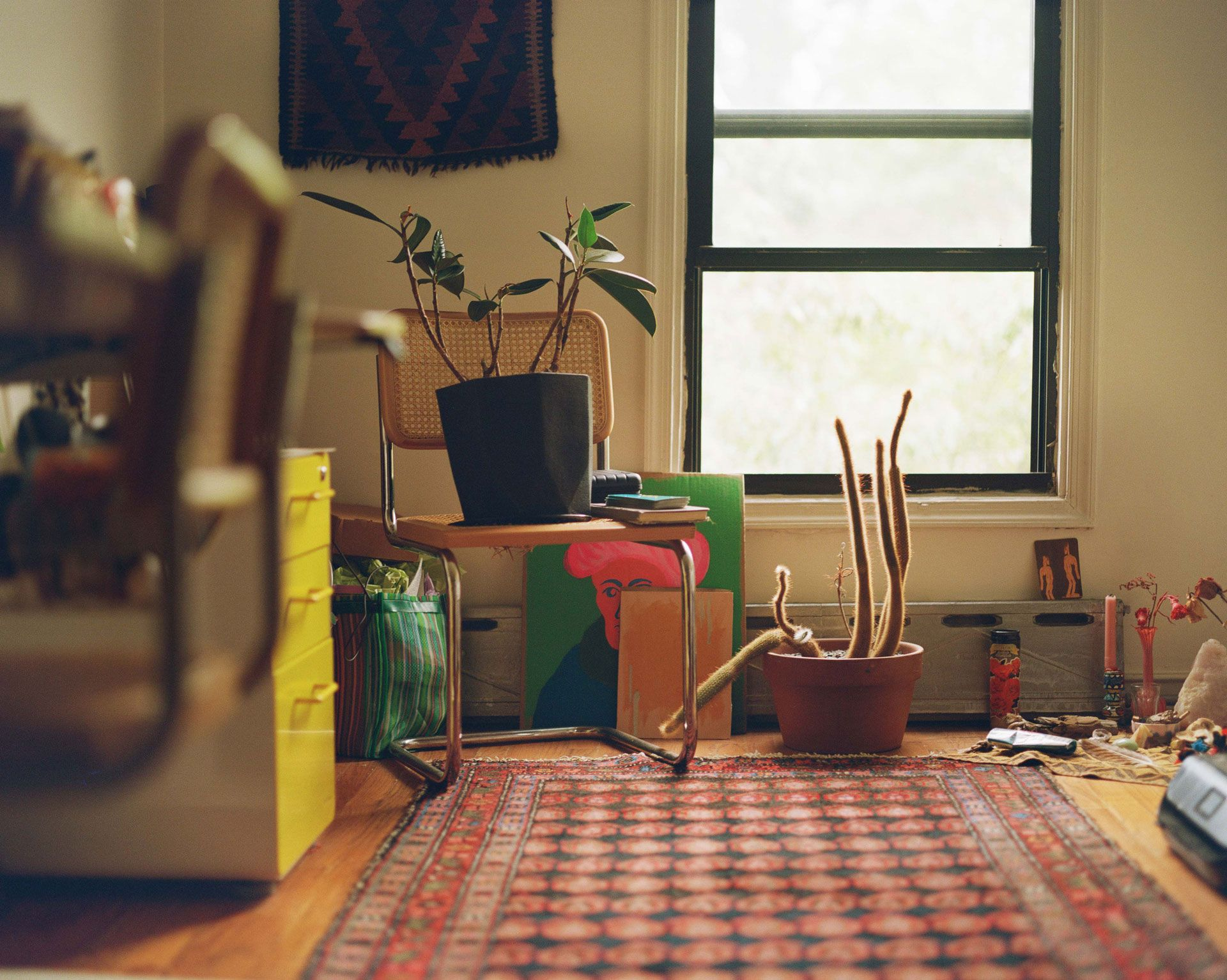 living room of writer Fariha Roisin with potter plant on rotin chair photographed by Oumayma B. Tanfous for Levi's