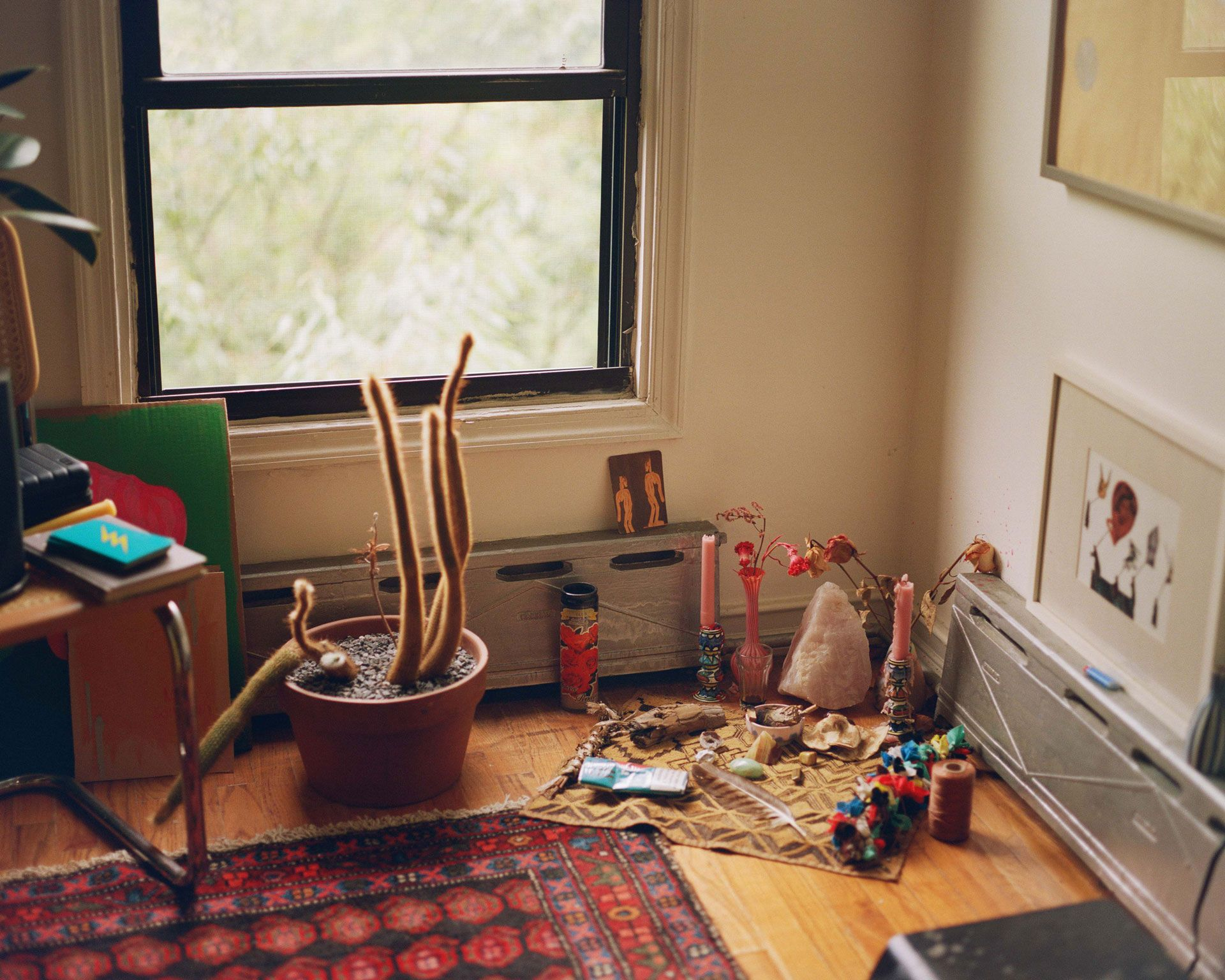 living room of writer Fariha Roisin displaying her altar on the ground filled with candles crystals and a feather photographed by Oumayma B. Tanfous for Levi's