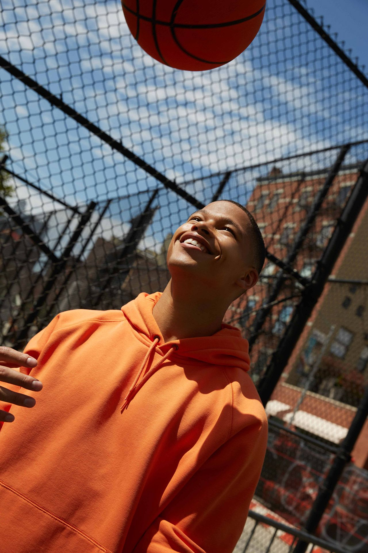 young black male model on outside basketball court smiling in the sun throwing basket ball into the air wearing bright orange hoodie photographed by Oumayma B Tanfous for Samsung phone campaign